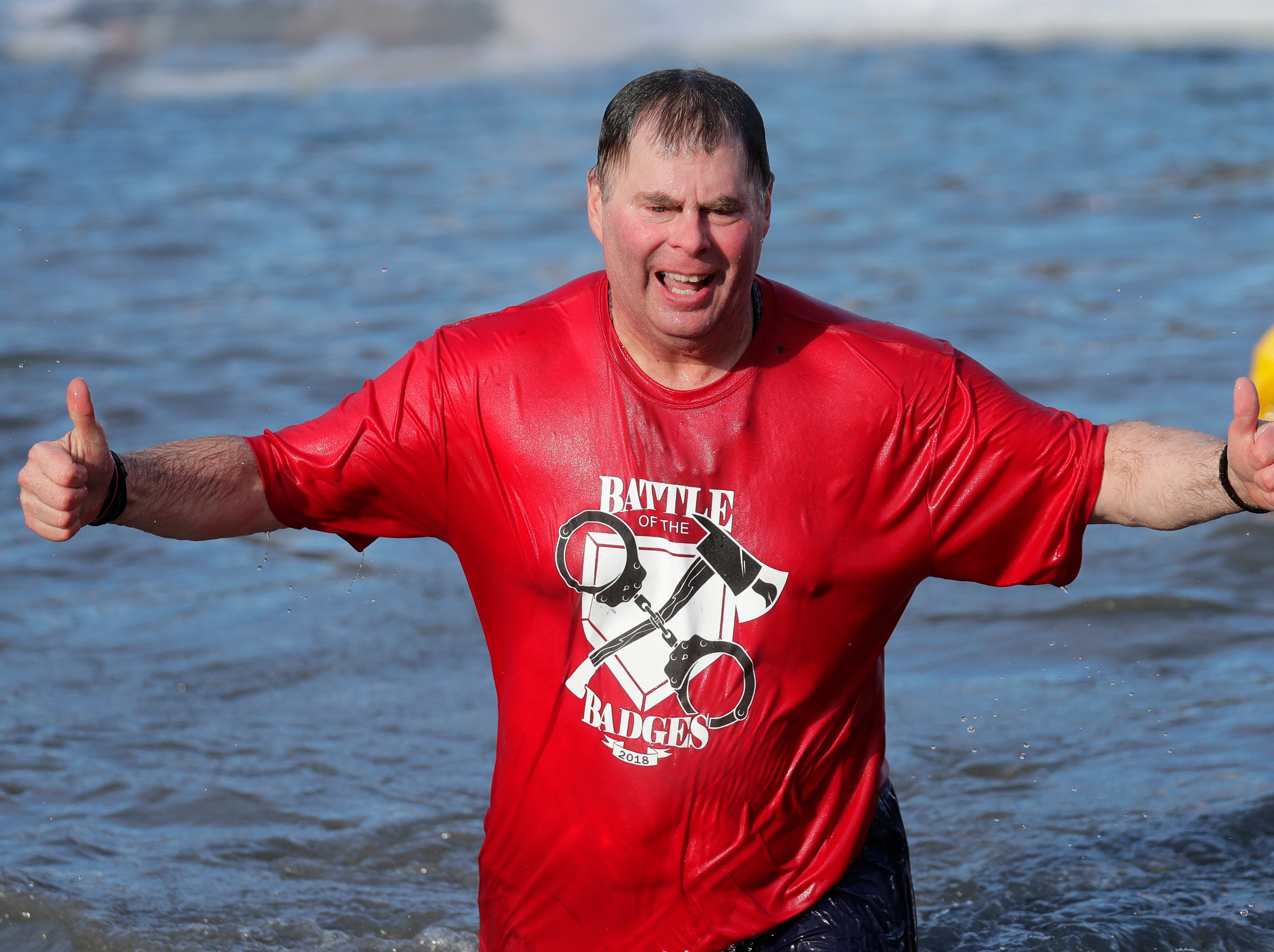 Lt. Pete Jungers of the Waupaca Fire Department gives a thumbs up during the Polar Bear Plunge Tuesday, January 1, 2019, at Becker Marine on Lime Kiln Lake in Waupaca, Wis. 