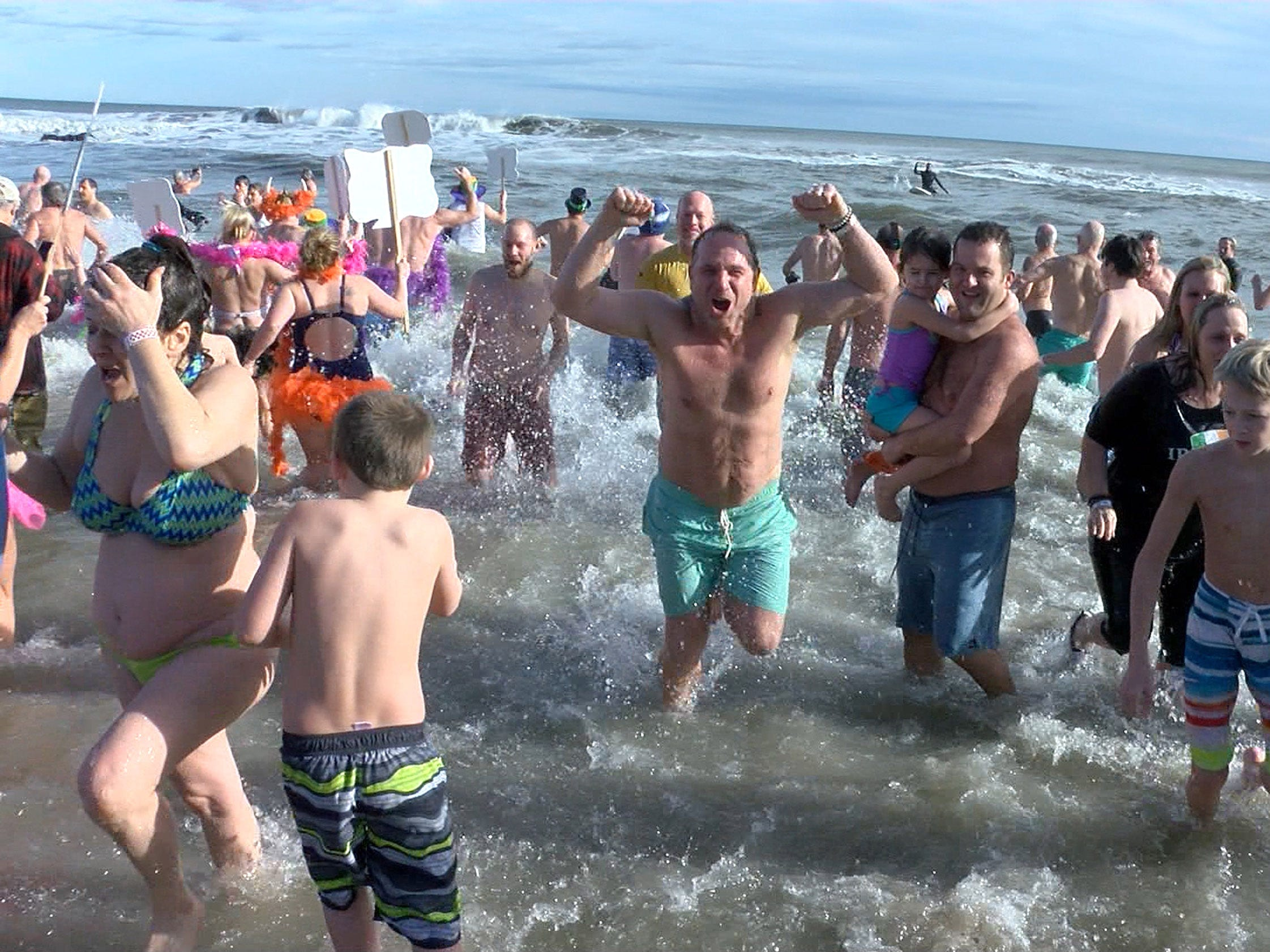 People celebrate after taking their New Years Day dip in the ocean off Asbury Park during the Sons of Ireland Polar Plunge Tuesday, January 1, 2019.
