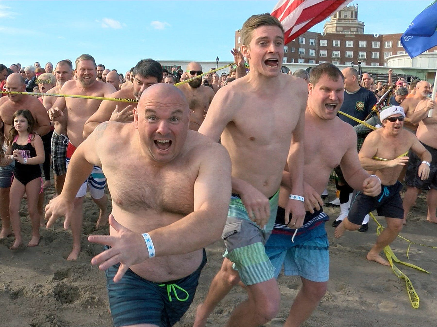 People run to take their New Years Day dip in the ocean off Asbury Park during the Sons of Ireland Polar Plunge Tuesday, January 1, 2019.