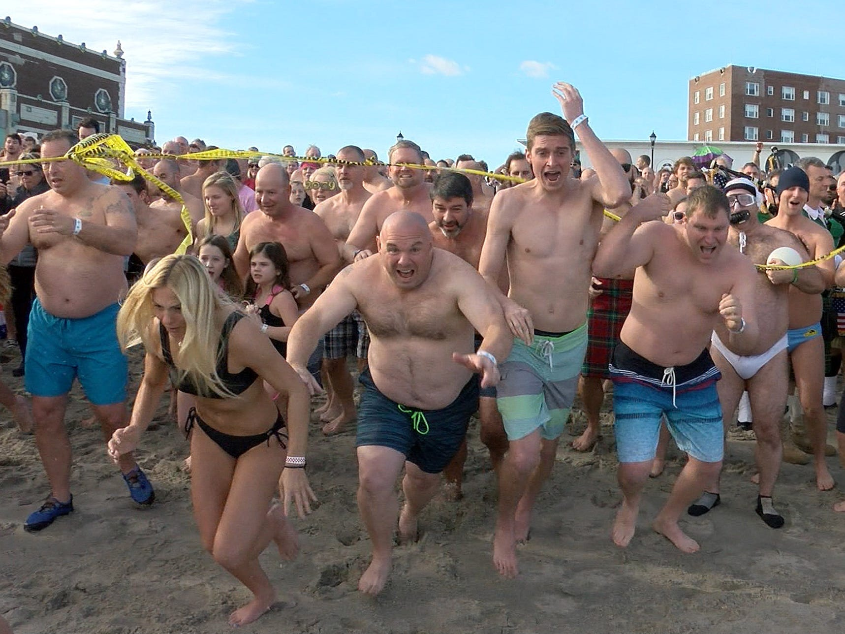 People sprint to the shoreline for their New Years Day dip in the ocean off Asbury Park during the Sons of Ireland Polar Plunge Tuesday, January 1, 2019.