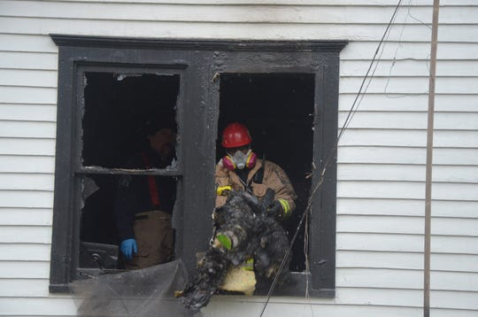 Battle Creek Fire Marshal Quincy Jones, right, and Police Detective Ryan Strunk clear debris from the living room as the search for evidence in the shooting death of a man found in his burning house.