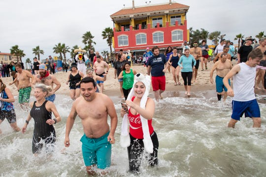 People run in to the Corpus Christi Bay on North Beach as they take part in the annual New Years Day Polar Bear Plunge on Tuesday, Jan. 1, 2019.