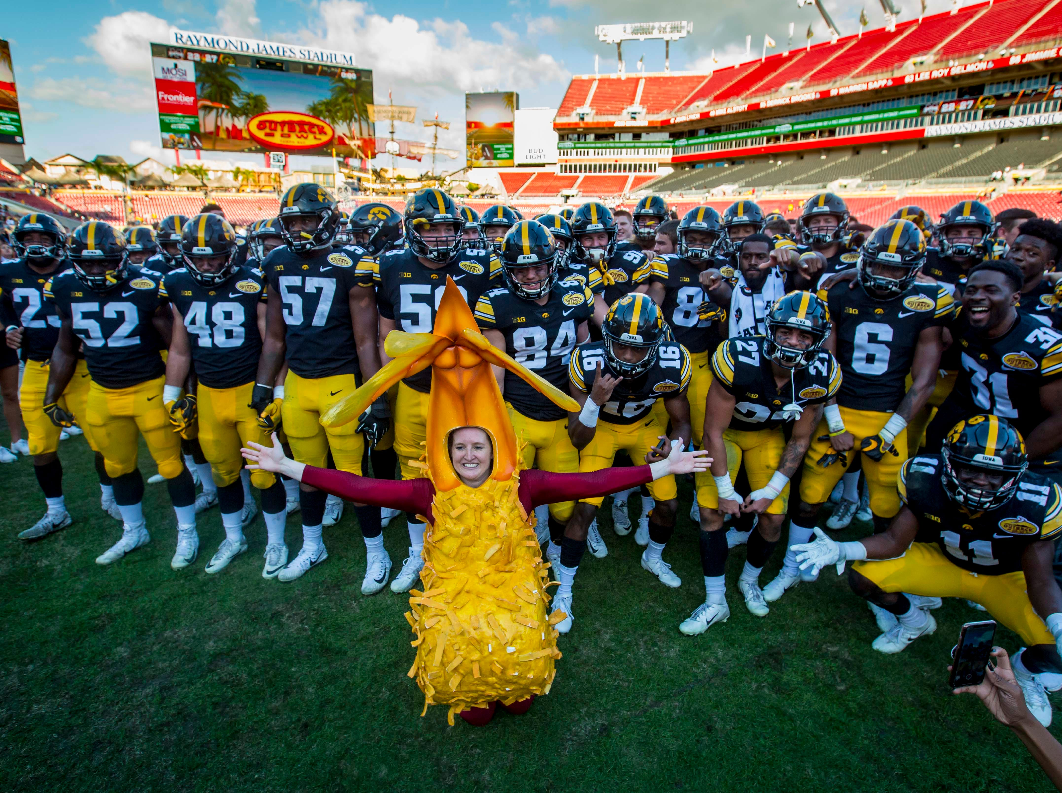 An Outback Bowl mascot with Iowa football players celebrate their victory over Mississippi State at the Outback Bowl Tues., Jan. 1, 2019, at Raymond James Stadium in Tampa, Florida. Iowa defeated Mississippi State 27-22.
