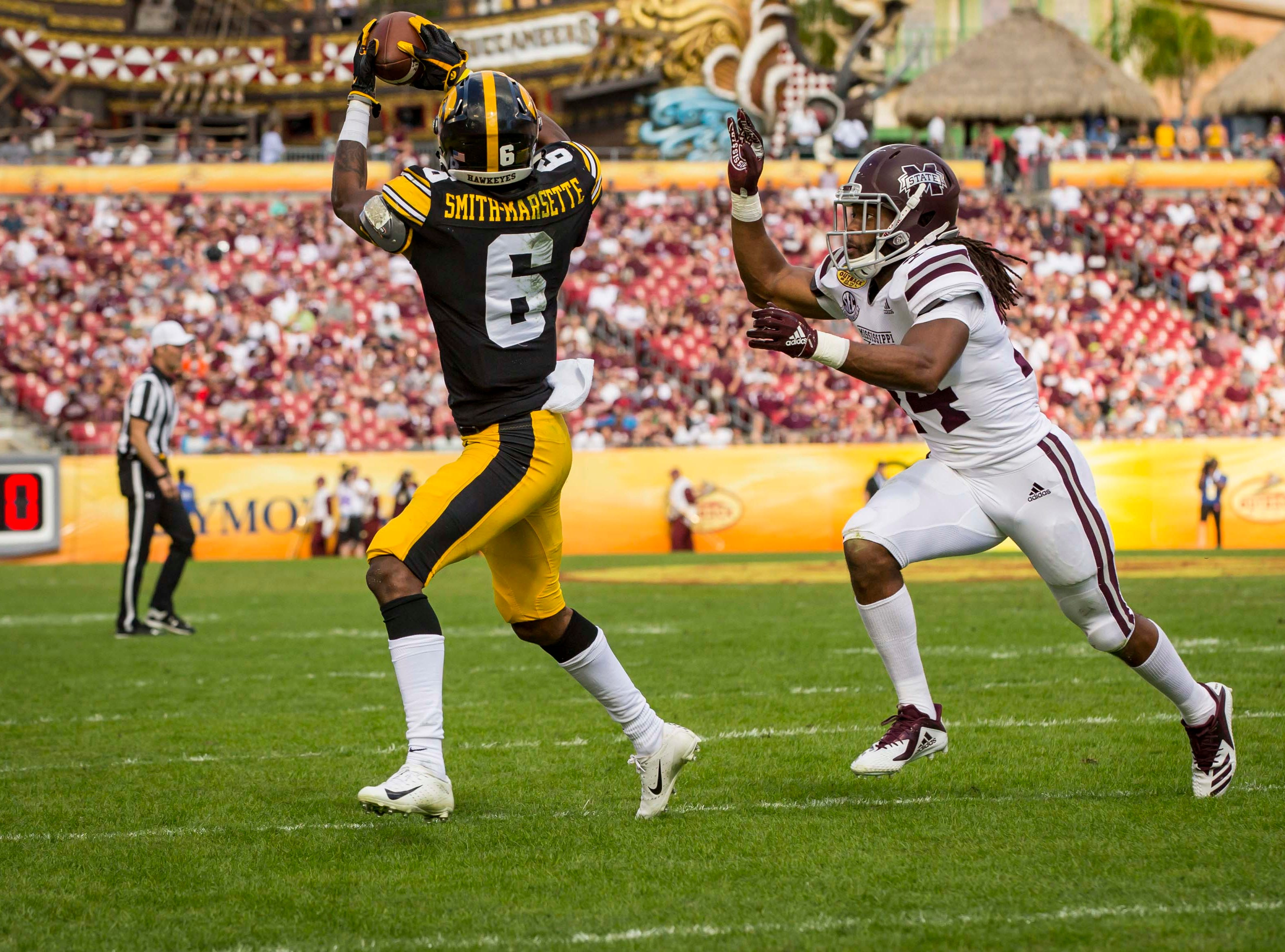 Iowa's wide receiver Ihmir Smith-Marsette catches a touchdown pass in front of Mississippi State's Chris Rayford in the first half at the  Outback Bowl Tues., Jan. 1, 2019, at Raymond James Stadium in Tampa, Florida. Iowa takes a 17-6 lead over Miss. St. into halftime.