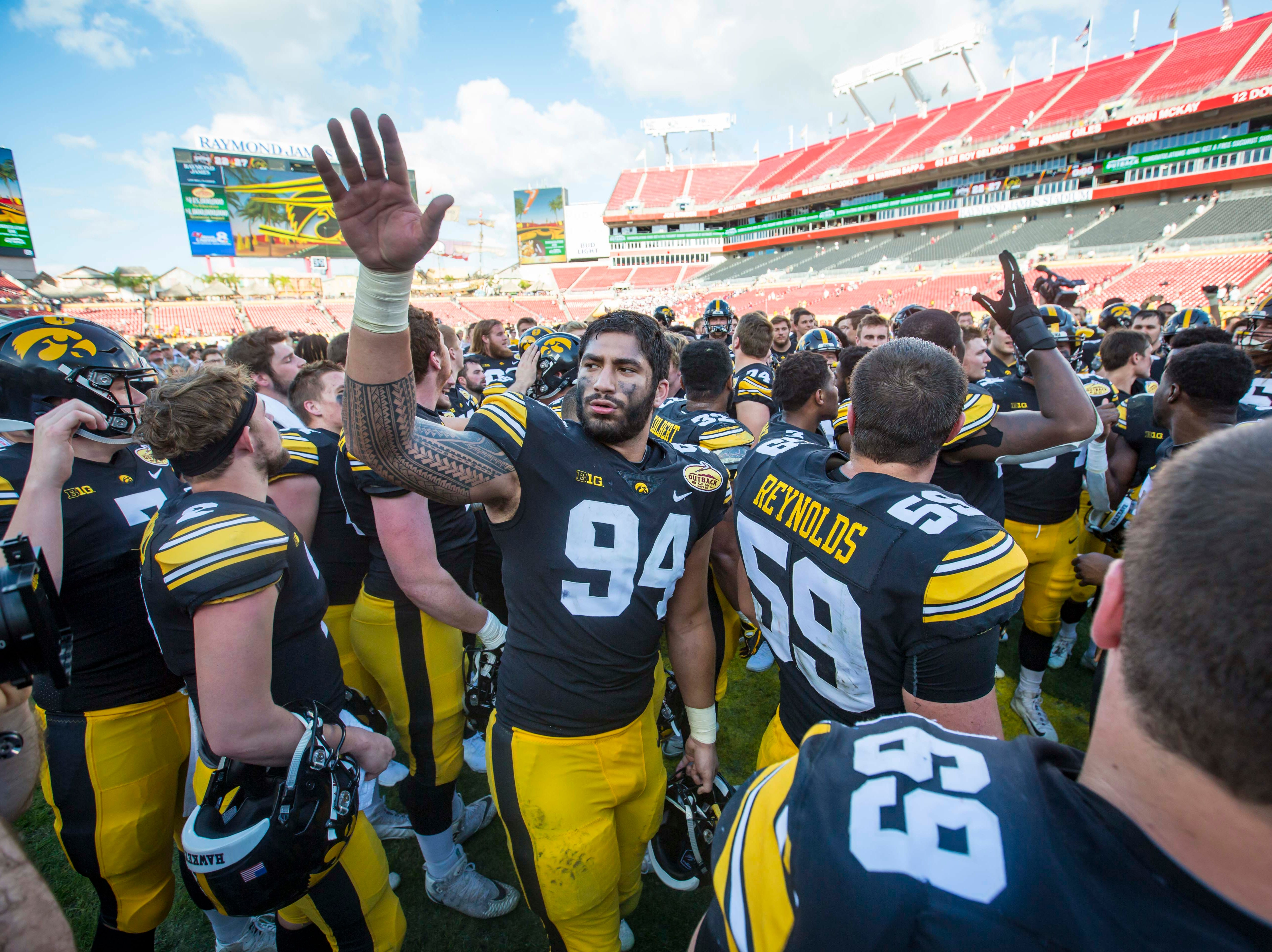 Iowa defensive end A.J. Epenesa celebrates with the team after their victory over Mississippi State at the Outback Bowl Tues., Jan. 1, 2019, at Raymond James Stadium in Tampa, Florida. Iowa defeated Mississippi State 27-22.