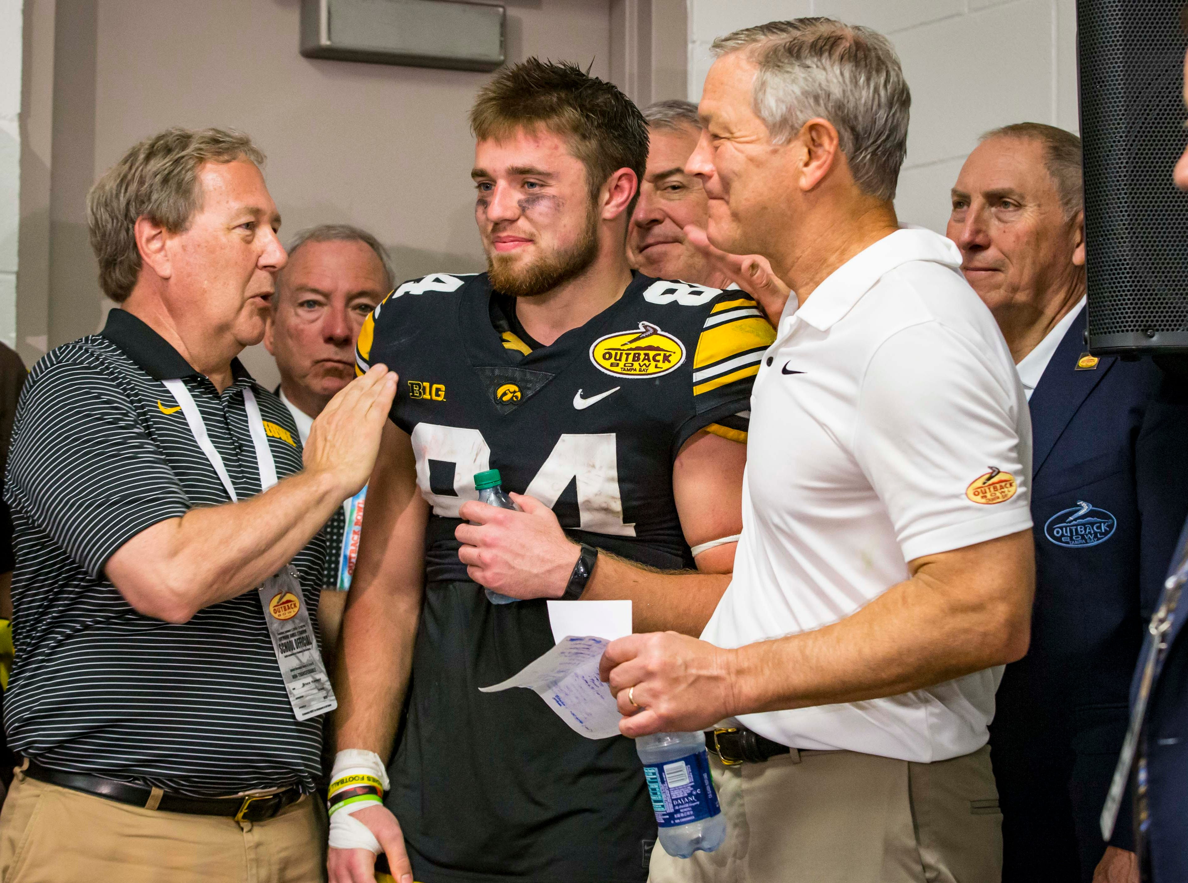 UI President Bruce Harreld, left, and coach Kirk Ferentz , right, congratulate Outback Bowl most valuable player Iowa wide receiver Nick Easley after the Outback Bowl Tues., Jan. 1, 2019, at Raymond James Stadium in Tampa, Florida. Iowa defeated Mississippi State 27-22.