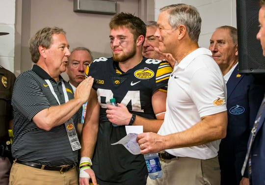 Iowa president Bruce Harreld (left) and football caoch Kirk Ferentz congratulate wide receiver Nick Easley after he was named MVP of Tuesday's Outback Bowl. Easley caught eight passes for 104 yards and two touchdowns in the finest, and final, game of his Hawkeye career.