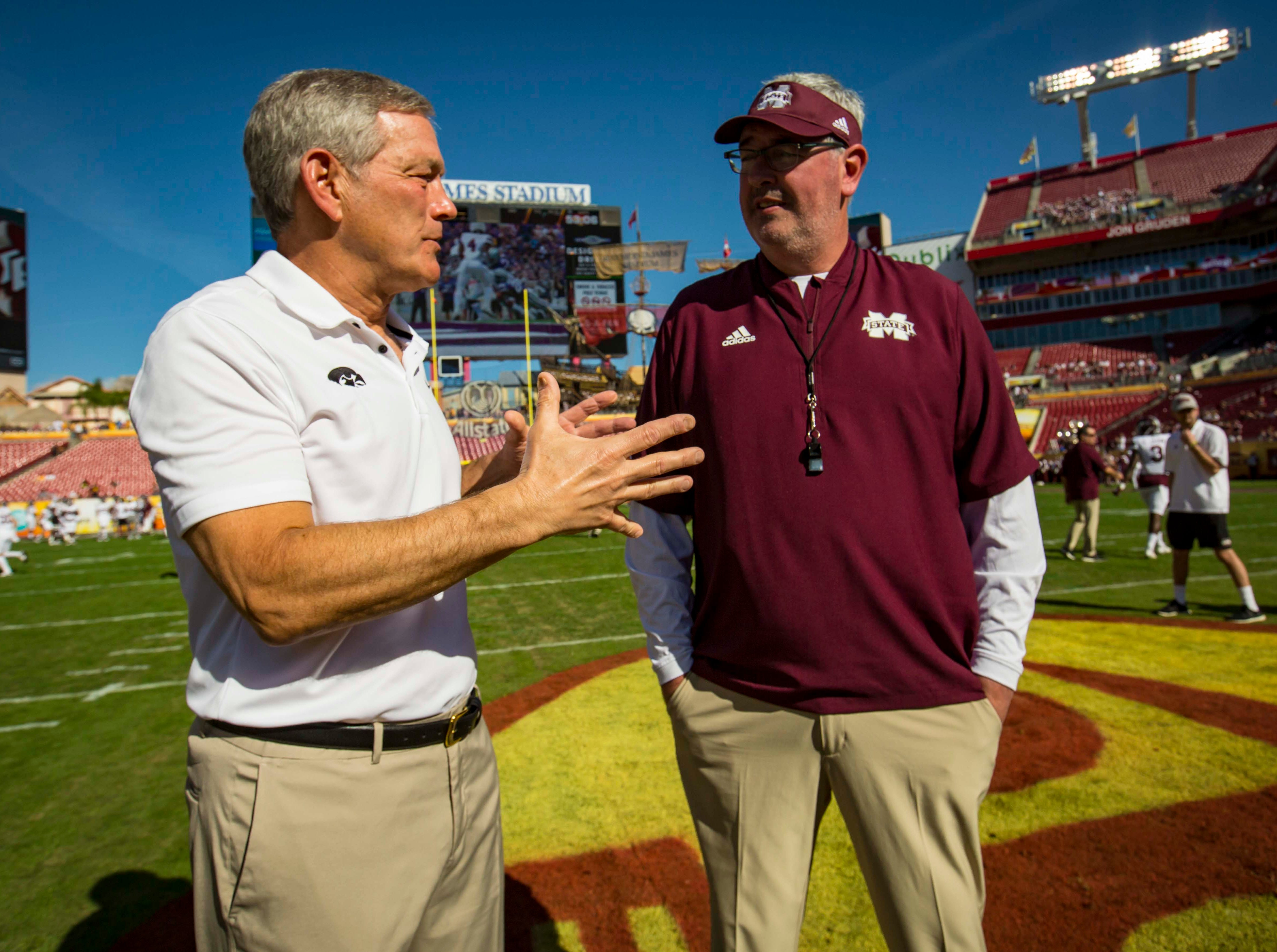 Iowa coach Kirk Ferentz and Mississippi State coach Joe Moorhead meet at midfield at the Outback Bowl Tues., Jan. 1, 2019, at Raymond James Stadium in Tampa, Florida.