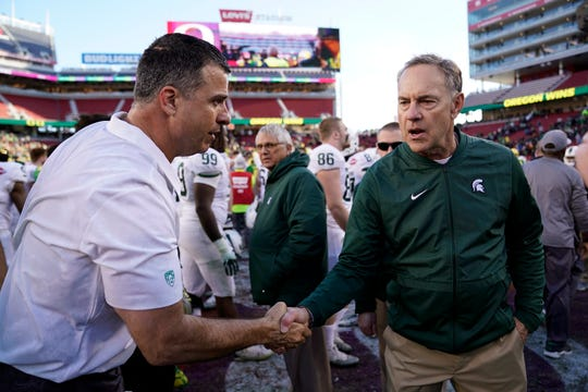 Oregon coach Mario Cristobal, left, shakes hands with Michigan State coach Mark Dantonio after the Redbox Bowl.