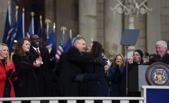 Michigan Governor Gretchen Whitmer hugs her husband Marc Mallory Tuesday, Jan. 1, 2019, after being sworn-in as Michigan's 49th governor on the steps of the State Capitol in Lansing, Michigan.  Also pictured are (from left: daughters Sydney and Sherry, Lt. Gov. Garlin Gilchrist.  Pictured on the right is former Gov. Rick Snyder.