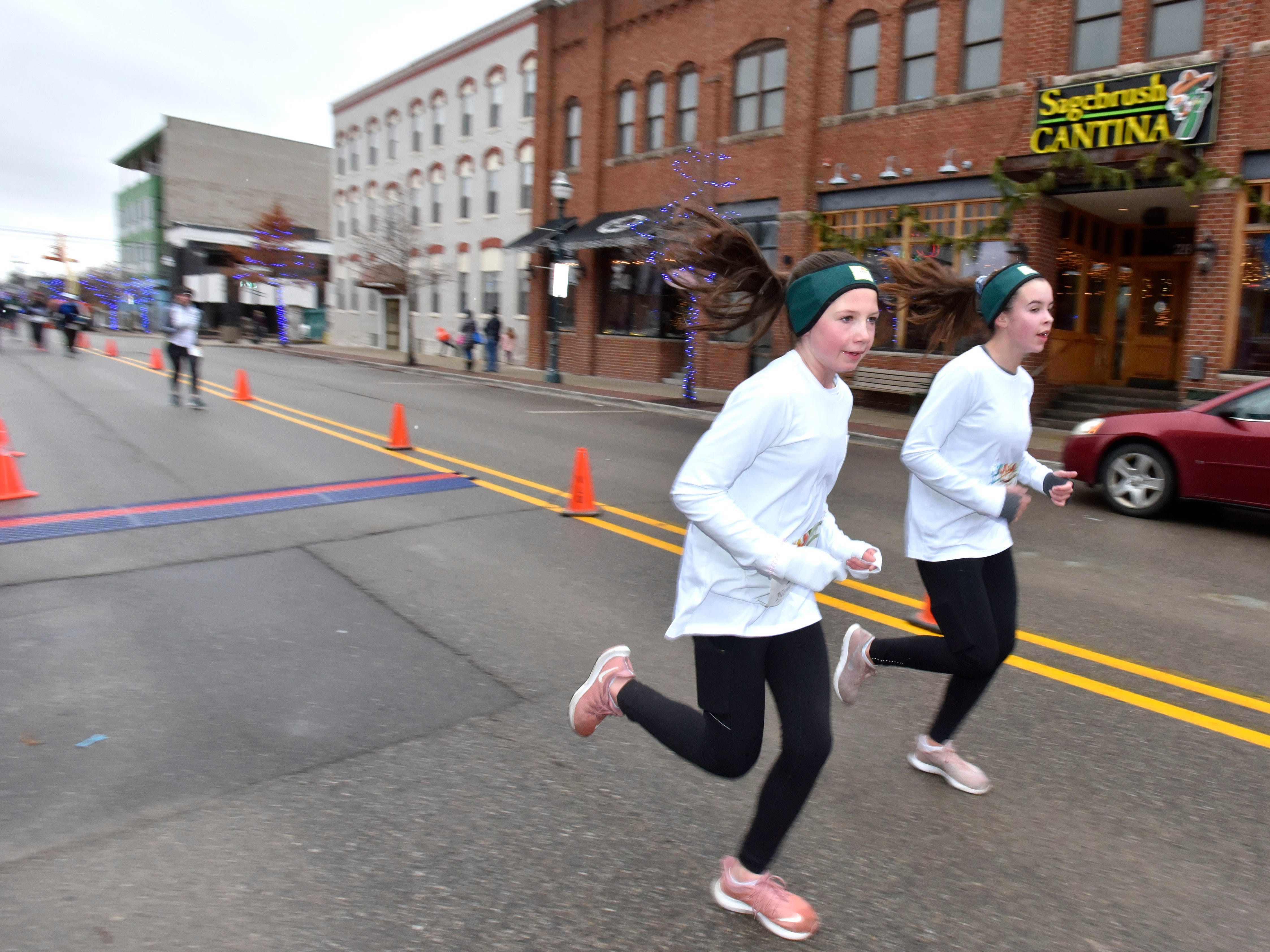 Cameron Cole (107), left, finishes 3rd in females ages 13 and under and 89th overall as Emmalee Clow (106), right, finishes 4th in females ages 13 and under and 91st overall.