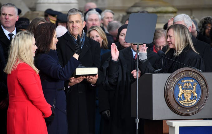 Gov. Gretchen Whitmer takes the oath of office on the steps of the Michigan Capitol in Lansing on Jan. 1, 2019. Witmer was joined by her daughters Sherry and Sydney while husband Marc Mallory holds the Bible.