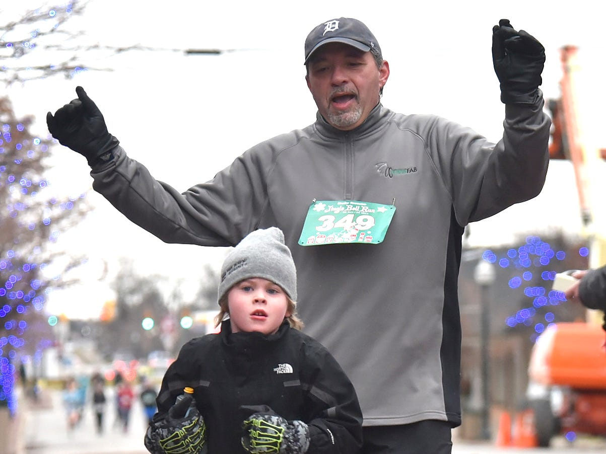 Norm Caetano (349), right, and his godson, Dylan Dyer (145), both of Rochester, cross the finish line, as Dyer, age 6, places second in the 1.5 mile run/walk with a time of 18:16.9 as Caetano, 58, places first in the 1.5 miler with a time of 17:51.5.