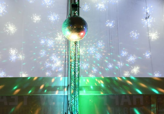 Lights reflect off of the large mirror ball after it drops at the New Year's Eve Kids Countdown.