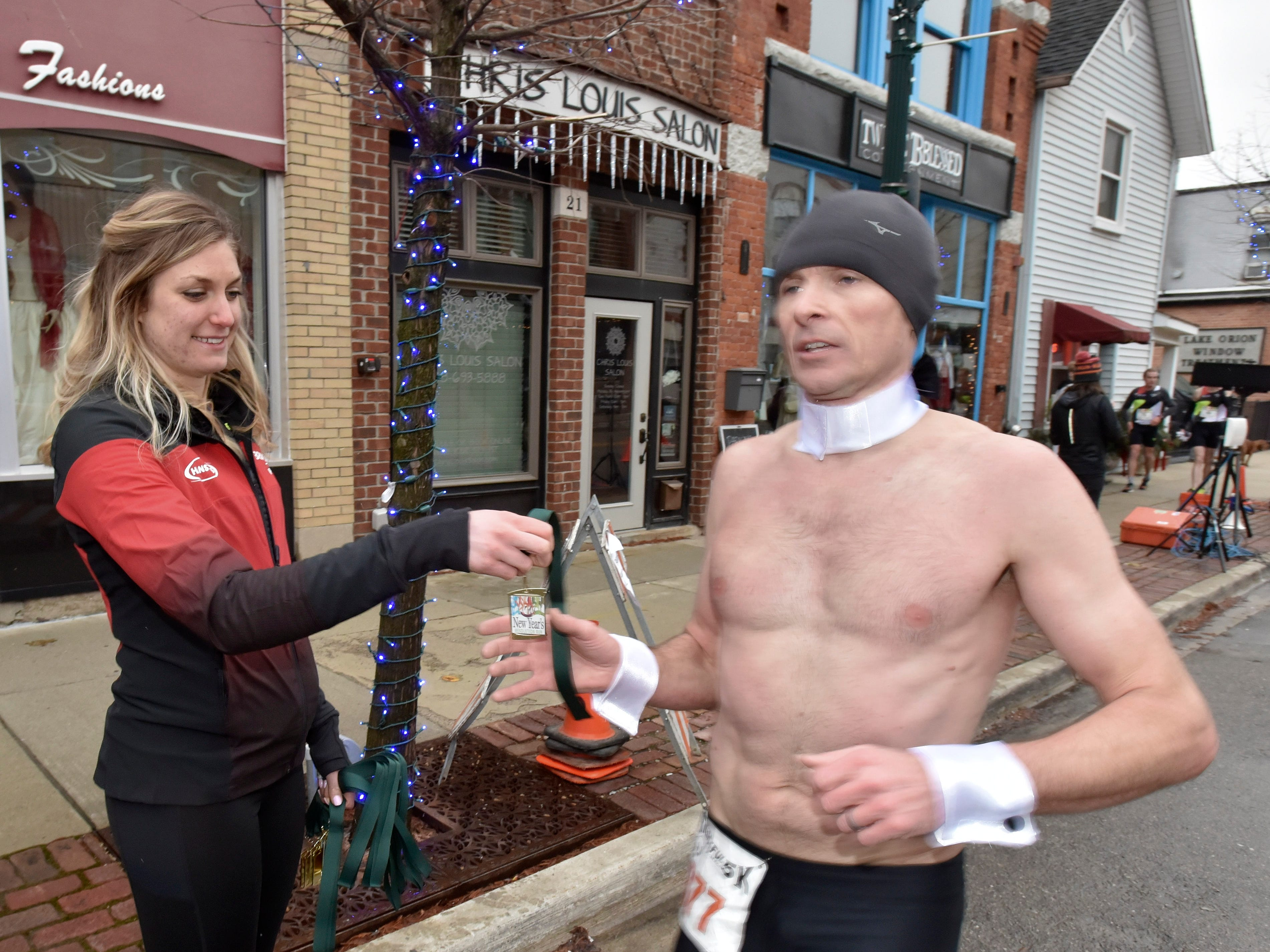 Hansons Brooks Distance Project professional running team member Rachele Schulist, left, of Rochester Hills, hands out a medal to Magic Mike (377) as he places first for males ages 30-39 and 10th overall.