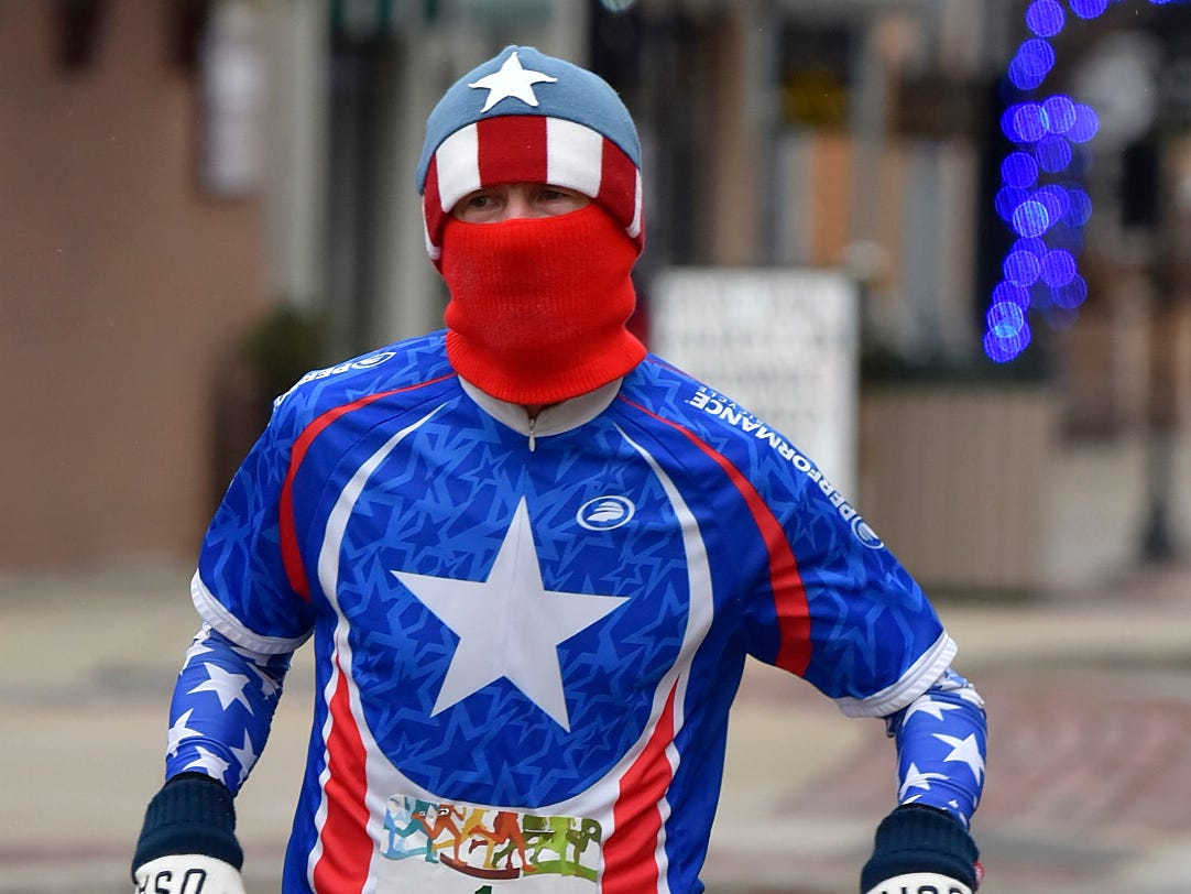 "Kevin ""Captain America"" Sherwood, 56, of Royal Oak, runs in his costume as he places 4th in males ages 50-59 and 26th overall."
