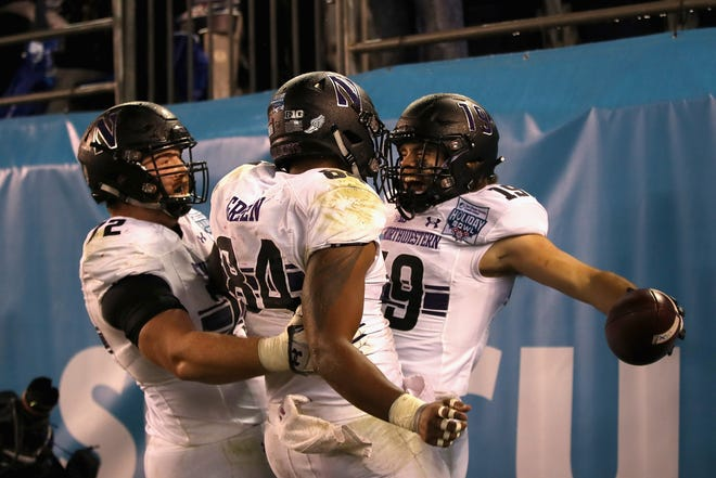 JJ Jefferson (12) and Cameron Green (84) congratulate Riley Lees (19) of the Northwestern Wildcats after his passing touchdown during the second half.