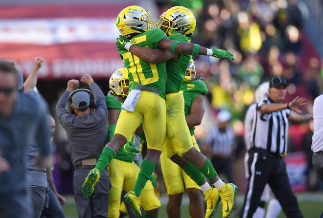 Thomas Graham Jr. (4) and Jaylon Redd (30) of the Oregon Ducks celebrate after Graham broke up a pass play to stop the Michigan State Spartans on fourth down late in the fourth quarter.