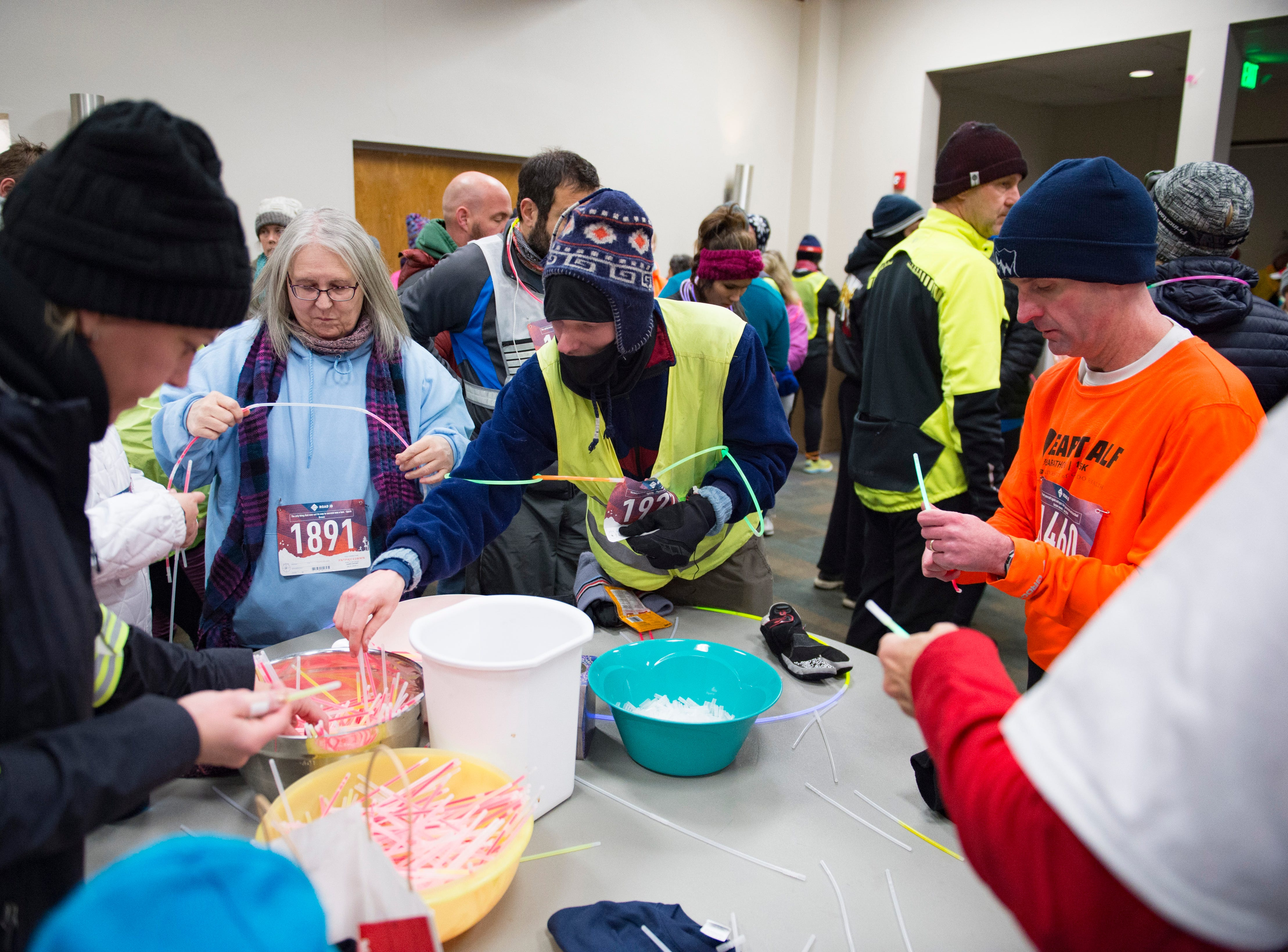 Runners grab glow-sticks before the Resolution Run 5K at Our Saviour's Lutheran Church on December 31, 2018. People braved single-digit temperatures to ring in the new year with the run.