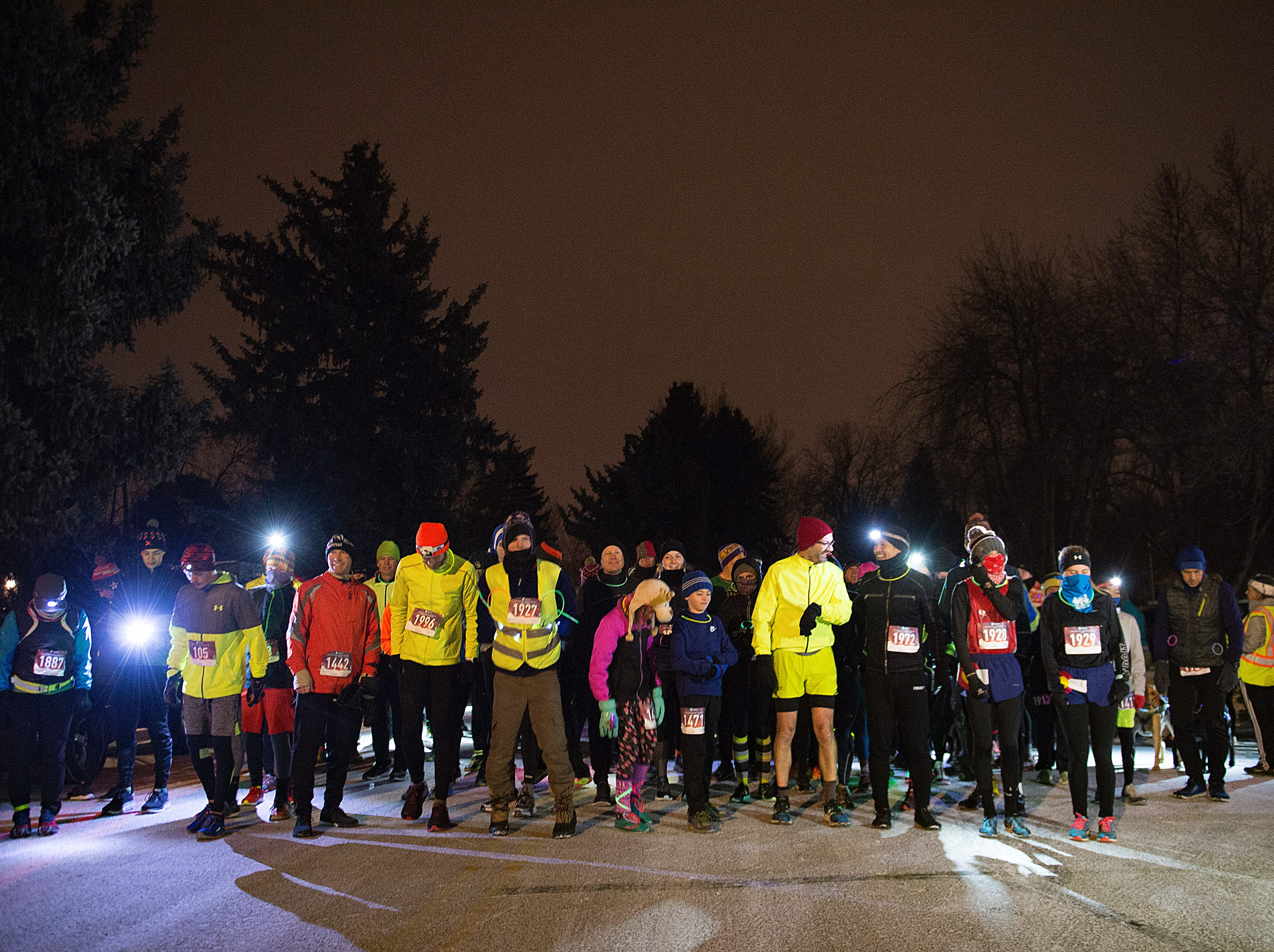 Runners line up on the snowy streets before beginning the Resolution Run 5K at Our Saviour's Lutheran Church on December 31, 2018. People braved single-digit temperatures to ring in the new year with the run.