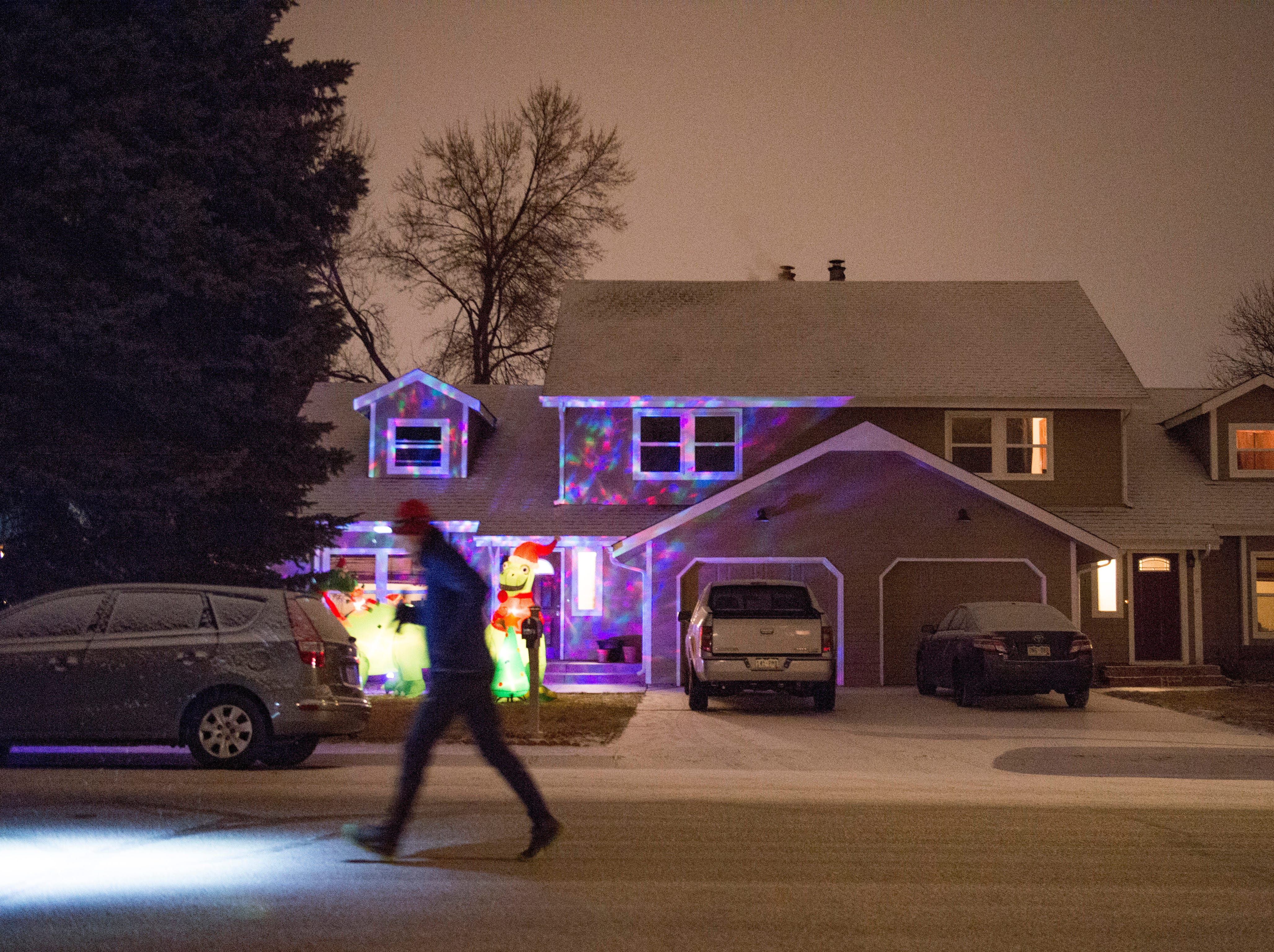 A runner passes a Christmas display in the dark during the Resolution Run 5K at Our Saviour's Lutheran Church on December 31, 2018. People braved single-digit temperatures to ring in the new year with the run.