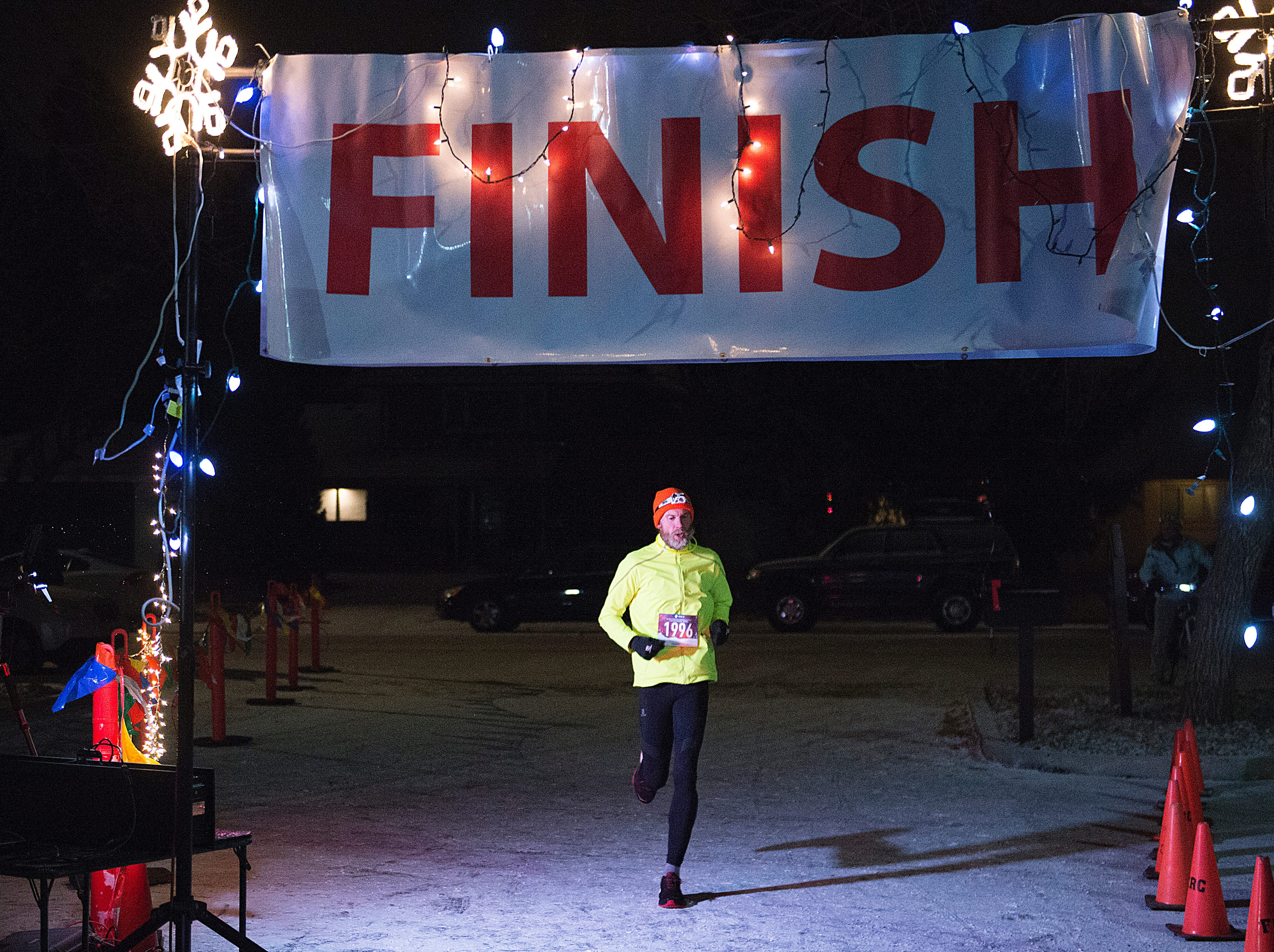 Race winner Stephen Pretak crosses the finish line for the Resolution Run 5K at Our Saviour's Lutheran Church on December 31, 2018. People braved single-digit temperatures to ring in the new year with the run.