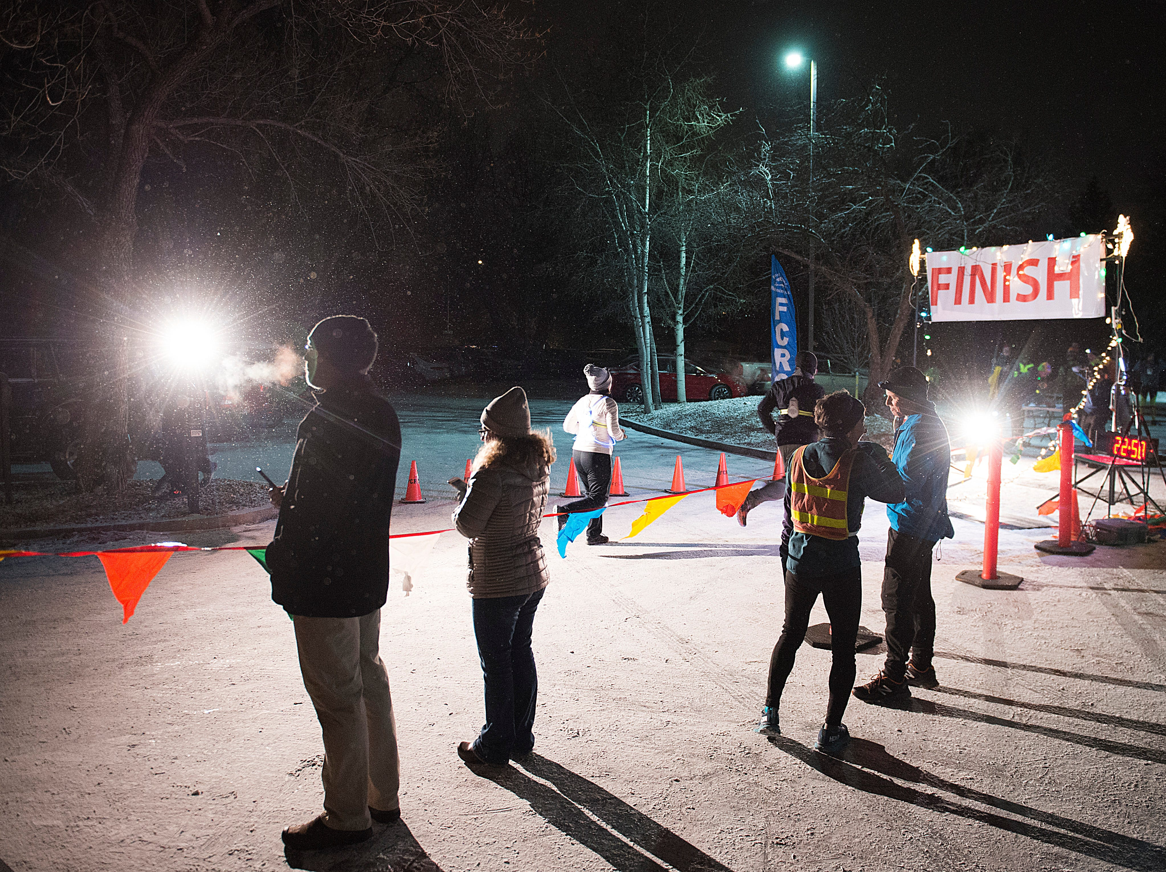 People cheer on runners as they cross the finish line in the Resolution Run 5K at Our Saviour's Lutheran Church on December 31, 2018. People braved single-digit temperatures to ring in the new year with the run.