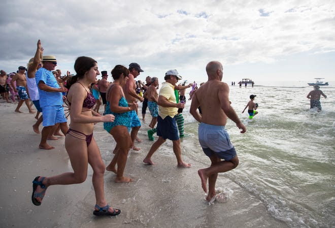 """Participants in the 14th annual Fort Myers Beach """"Polar Bear Dip"""" make their way to the water Tuesday afternoon. The fund raising event, held at the Outrigger Beach Resort, will benefit local beach resident Steve Miller who has been undergoing multiple surgeries/medical procedures and months of chemotherapy."""