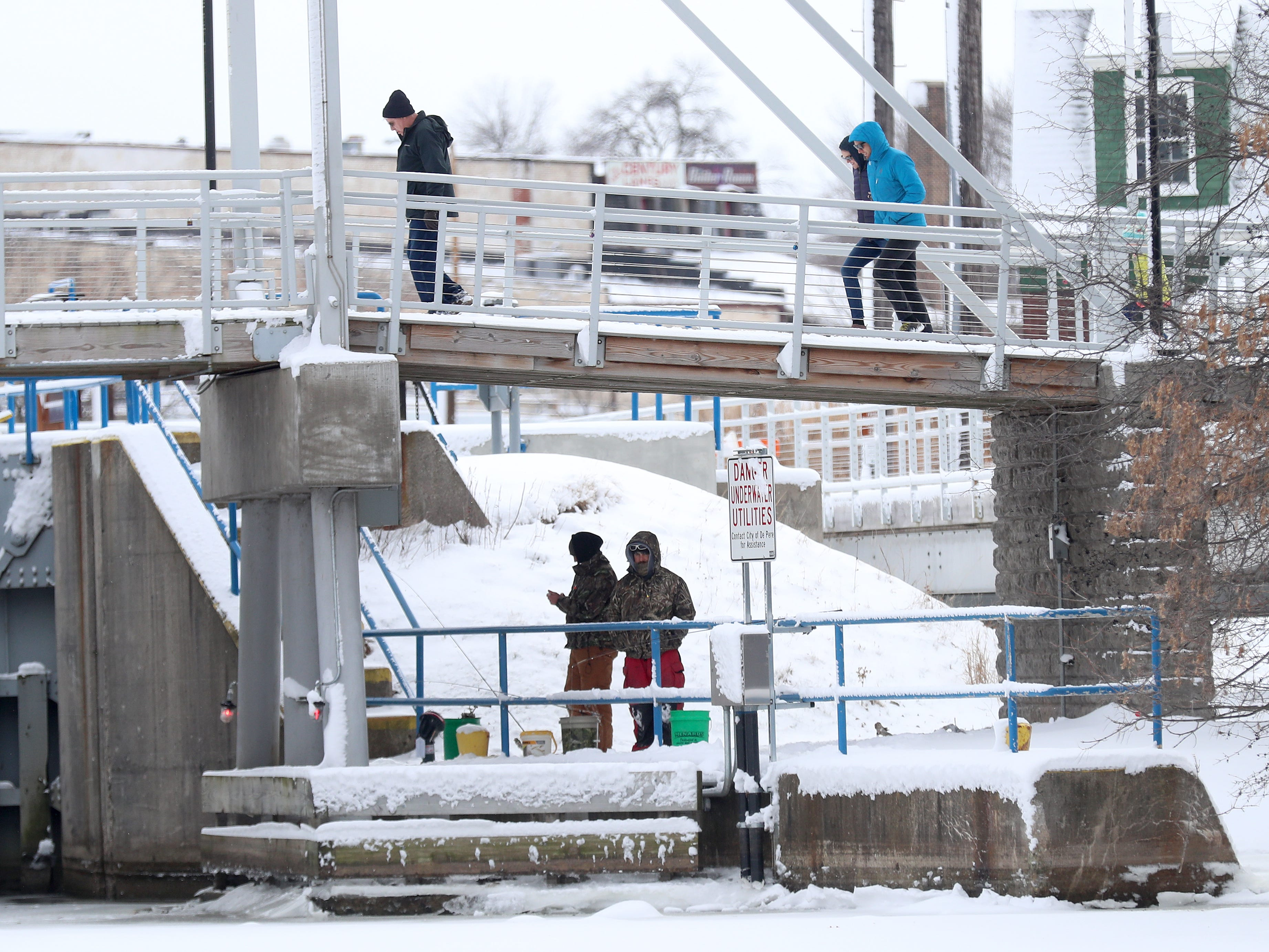 Snowy strollers and ice fishermen enjoy New Years Day at the De Pere lock adjacent to Voyageur Park Tuesday, January 1, 2019 in De Pere, Wis
