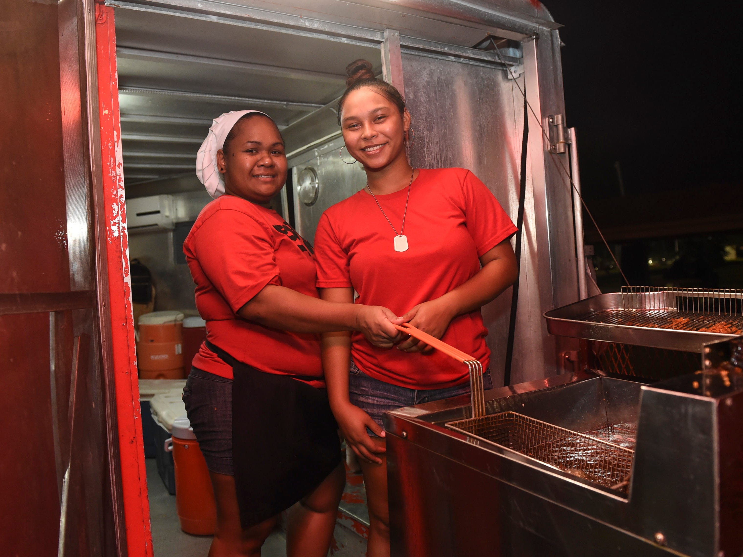 Sip N' Dip Guam and Shave It employees Jadene Ongesii, left, and Liela Evaristo during New Year's Eve at the Gov. Joseph Flores Beach Park on Dec. 31, 2018.