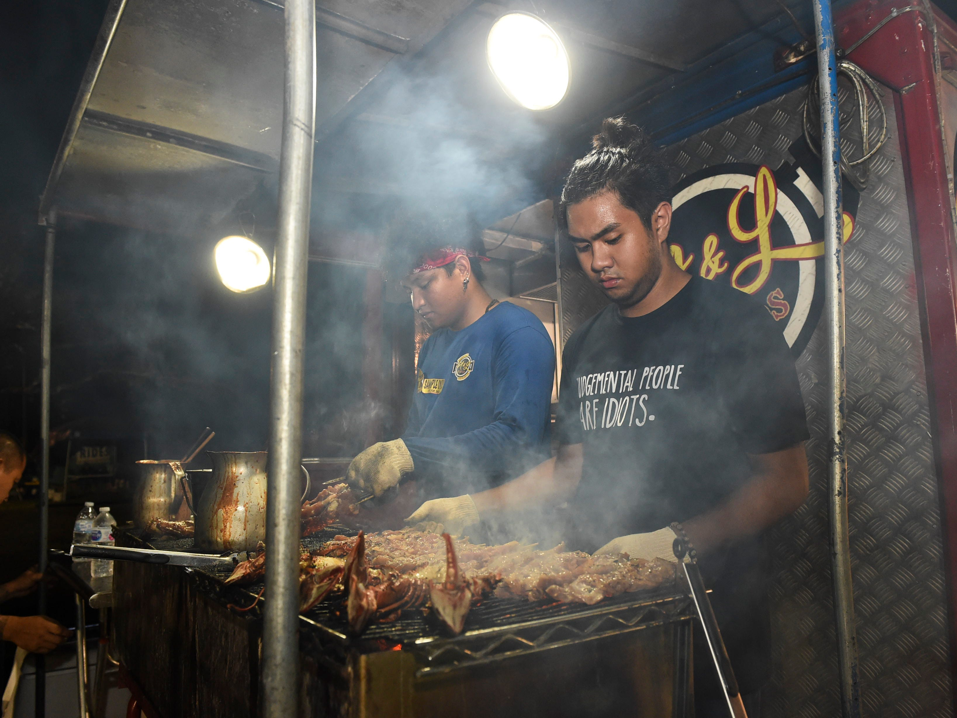 A&L Foods employees barbecue meat during New Year's Eve at the Gov. Joseph Flores Beach Park on Dec. 31, 2018.