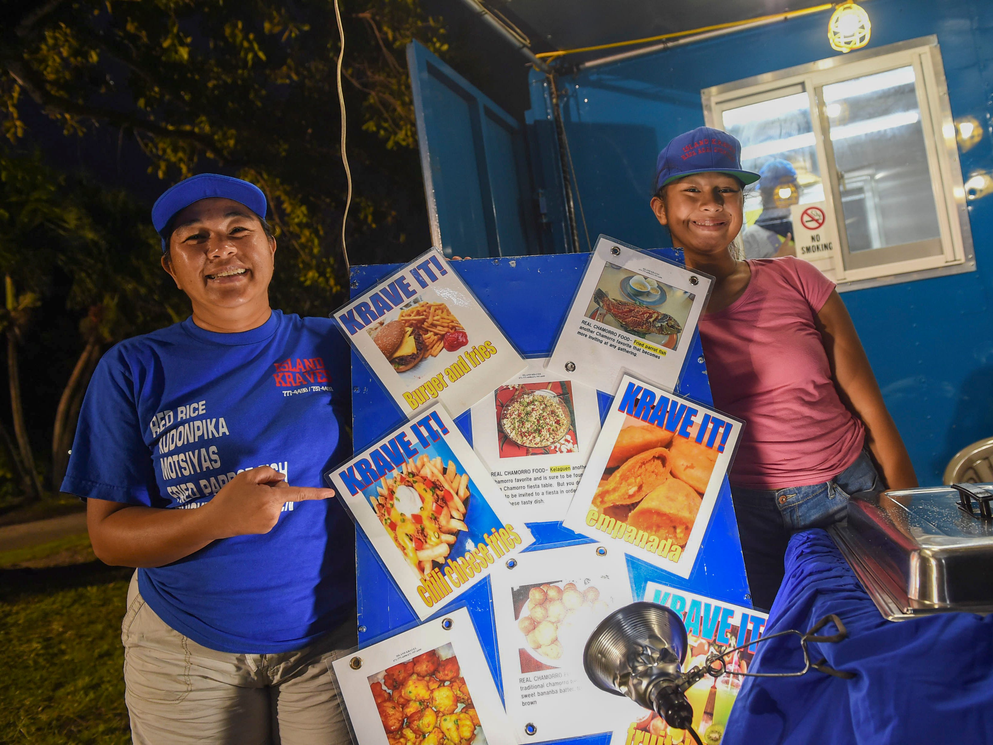 Island Kraves owner Therese Flores with her daughter Cherese at their local food truck during New Year's Eve at the Gov. Joseph Flores Beach Park on Dec. 31, 2018.