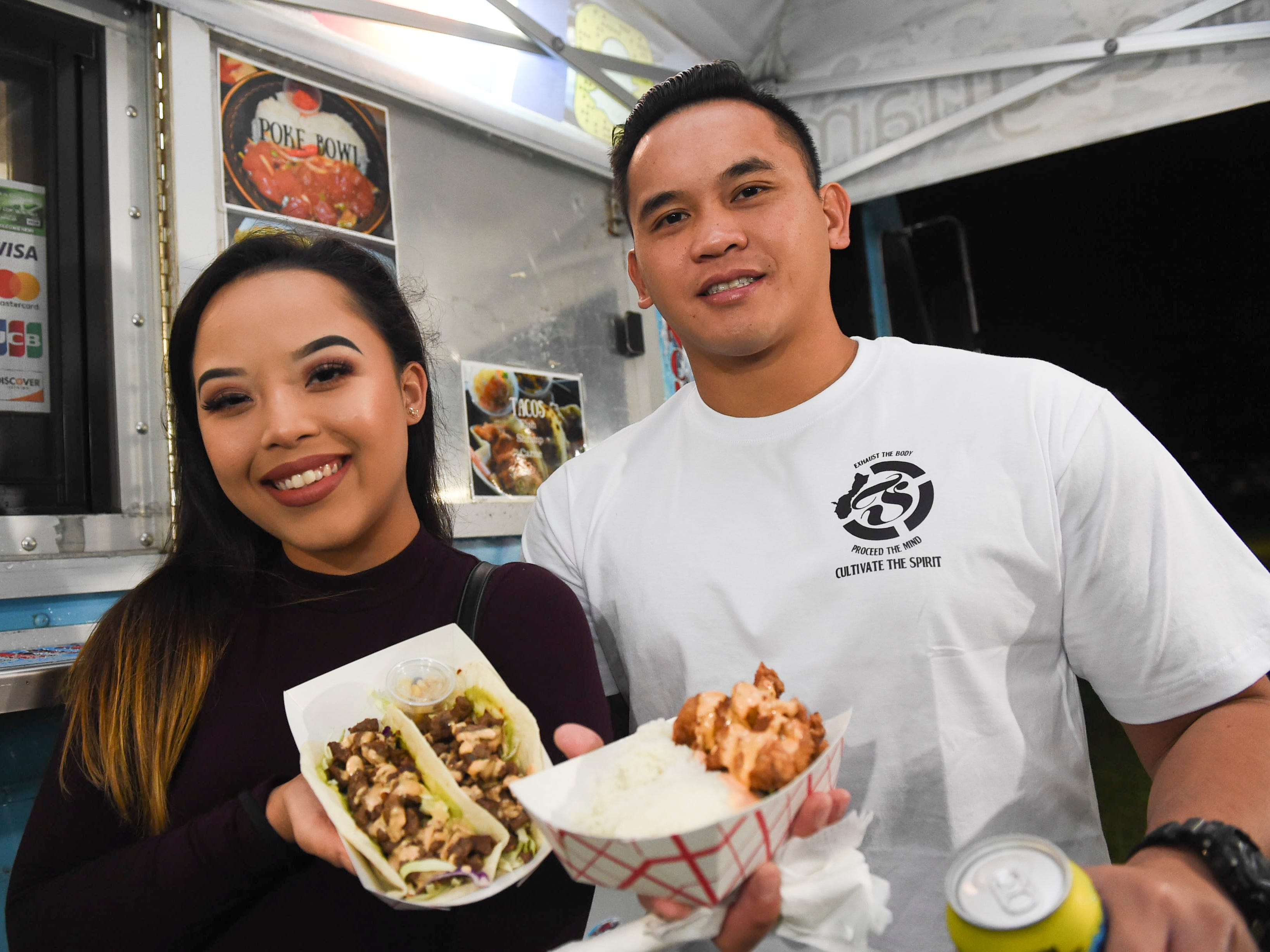 Elliot Untalan and Maelani Terlaje grab a bite to eat from Munchies Food Truck Guam during New Year's Eve at the Gov. Joseph Flores Beach Park on Dec. 31, 2018.