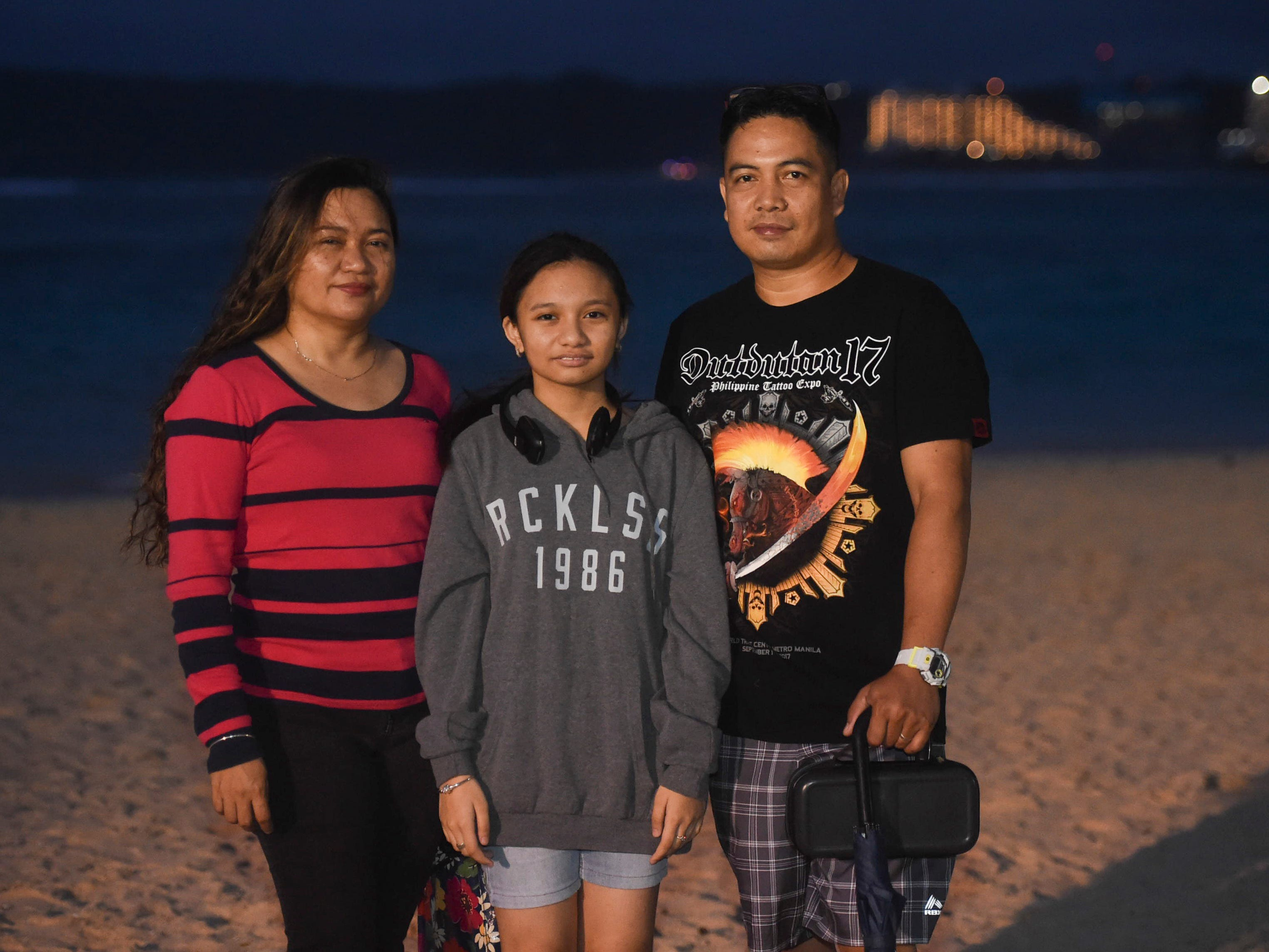 Allan Abella, right, with his wife Sheryll, and daughter Rosielyn, 13, spend New Year's Eve on the beach at the Gov. Joseph Flores Beach Park on Dec. 31, 2018.