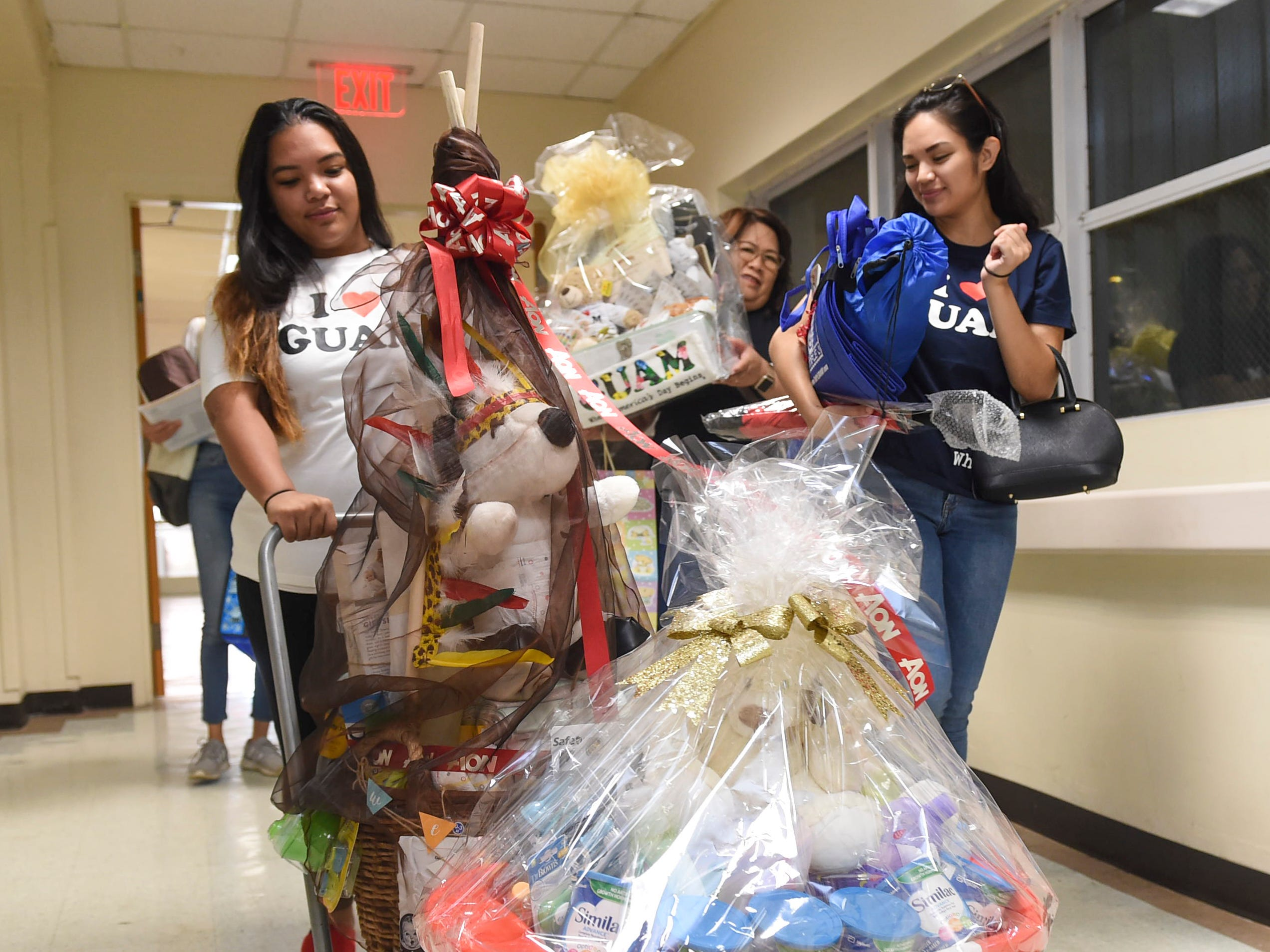 """Archway, Inc. members roll in baskets of gifts for the New Year's Day baby as part of the """"I Love Guam New Year Baby"""" program at Guam Memorial Hospital in Tamuning on Jan. 1, 2019."""