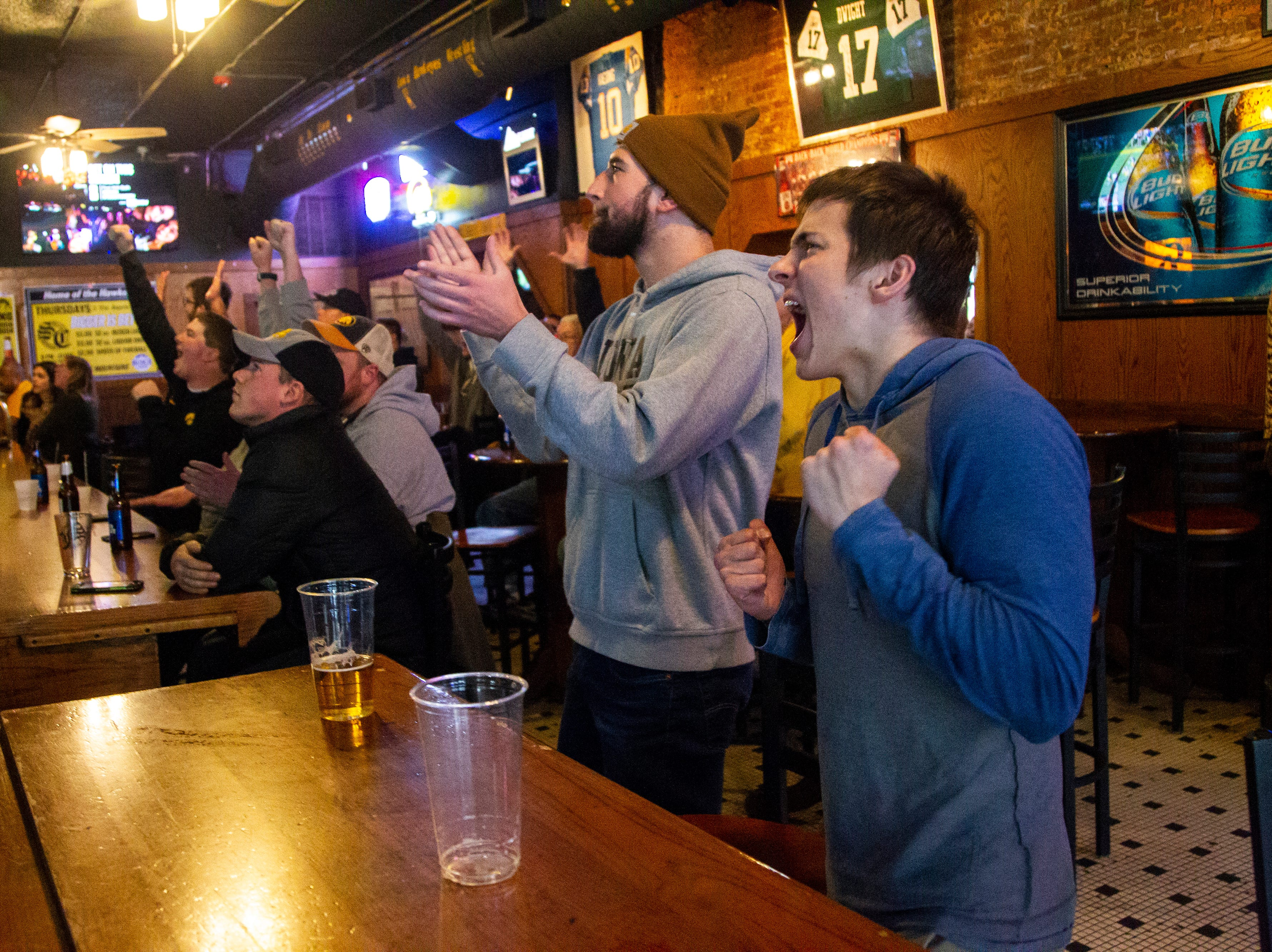 Iowa fans Casey Dauksas, right, and Nolan Stevens react while watching the Iowa vs. Mississippi State Outback Bowl football game on Tuesday, Jan. 1, 2019, at Sports Column on S. Dubuque Street in Iowa City.