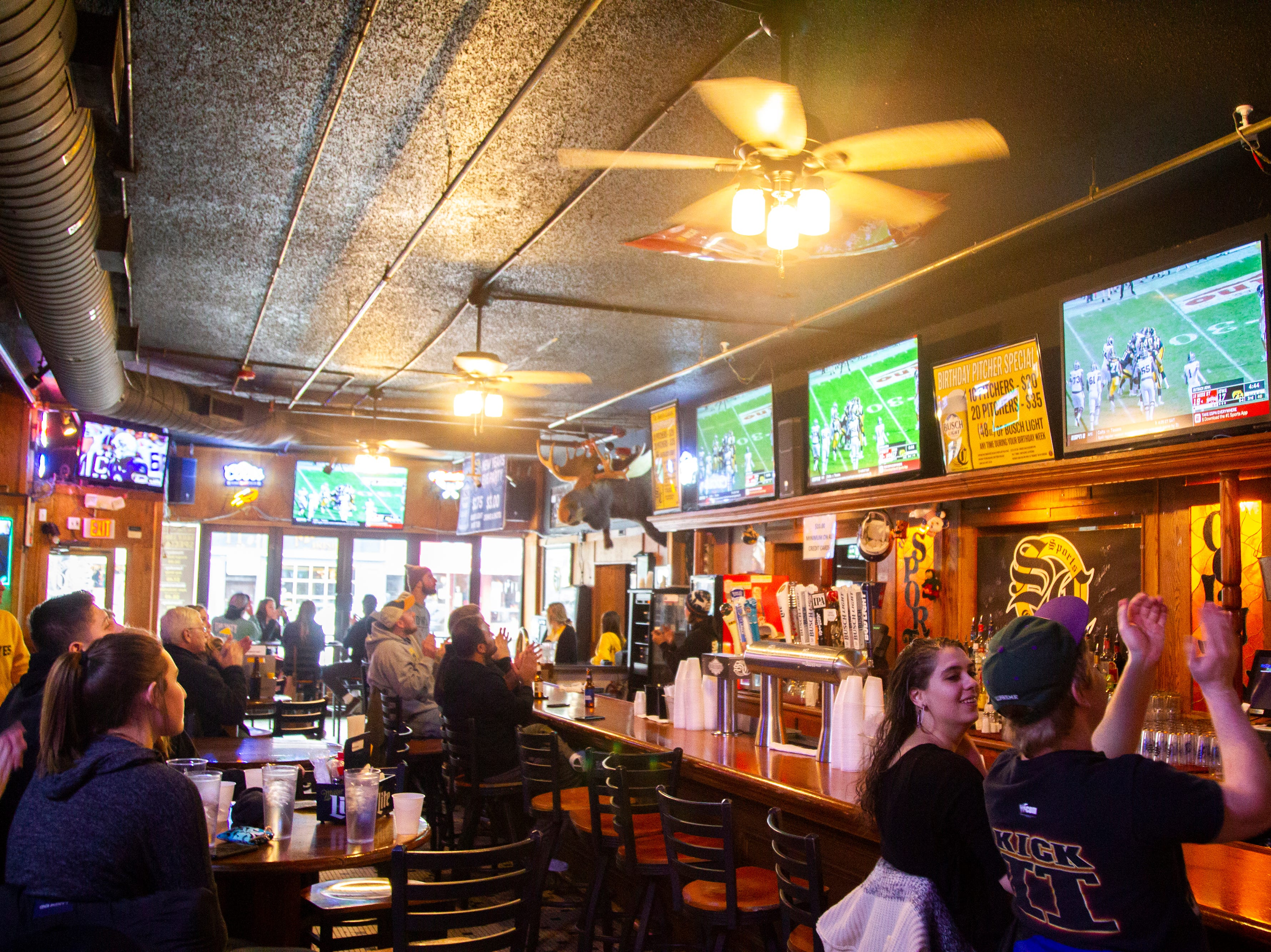 Fans react while watching the Iowa vs. Mississippi State Outback Bowl football game on Tuesday, Jan. 1, 2019, at Sports Column on S. Dubuque Street in Iowa City.