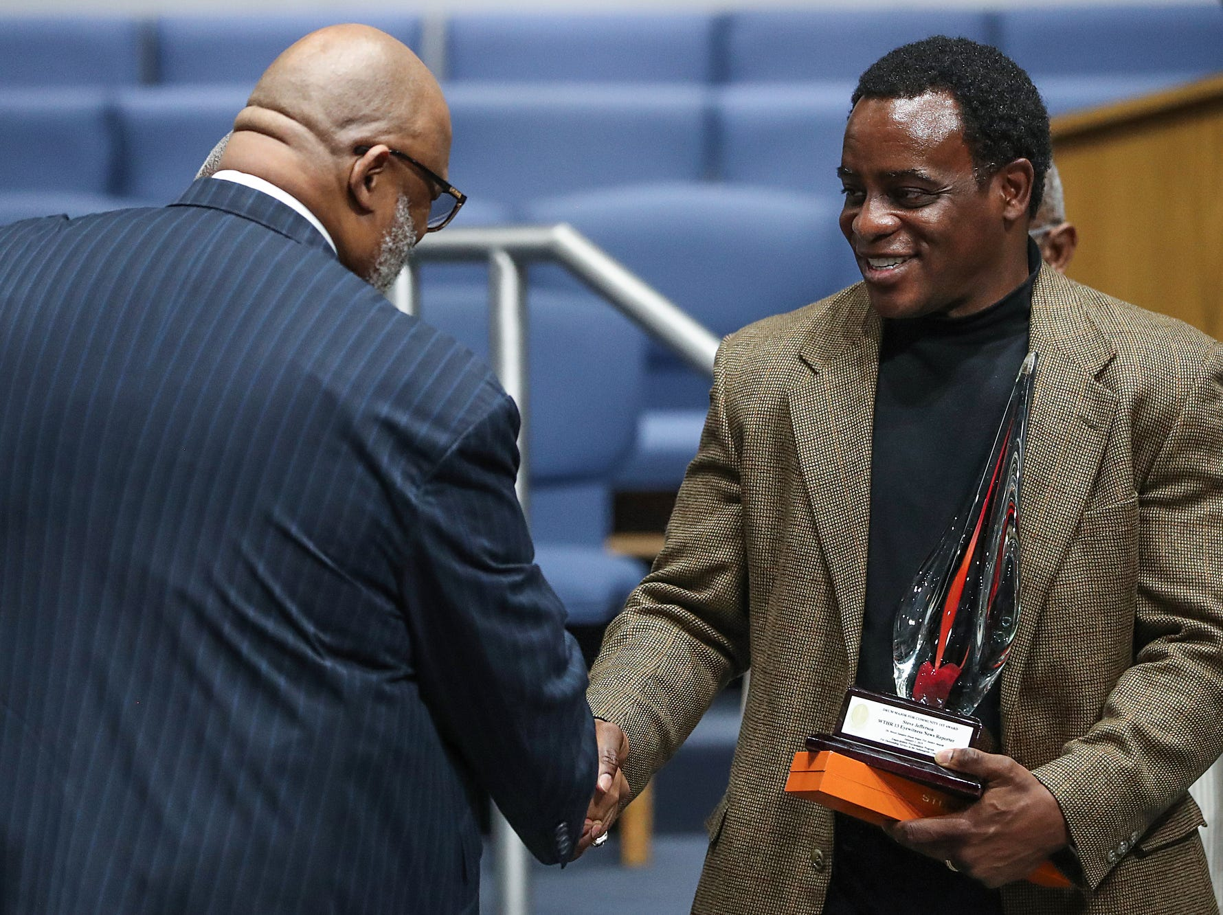 Rev. Dr. Wayne Moore hands the Community 1st Award to Steve Jefferson, during a service celebrating the anniversary of the Emancipation Proclamation at Olivet Missionary Baptist Church in Indianapolis, Tuesday, Jan. 1, 2019. Jefferson is a news reporter for WTHR Channel 13.