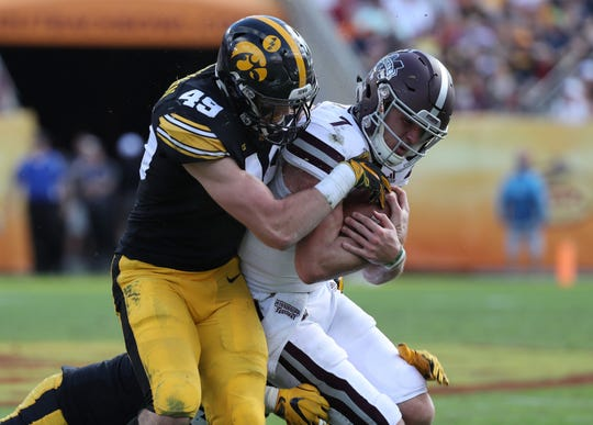 Jan 1, 2019; Tampa, FL, USA; Iowa Hawkeyes linebacker Nick Niemann (49) tackles Mississippi State Bulldogs quarterback Nick Fitzgerald (7) during the second quarter in the 2019 Outback Bowl at Raymond James Stadium. Mandatory Credit: Kim Klement-USA TODAY Sports