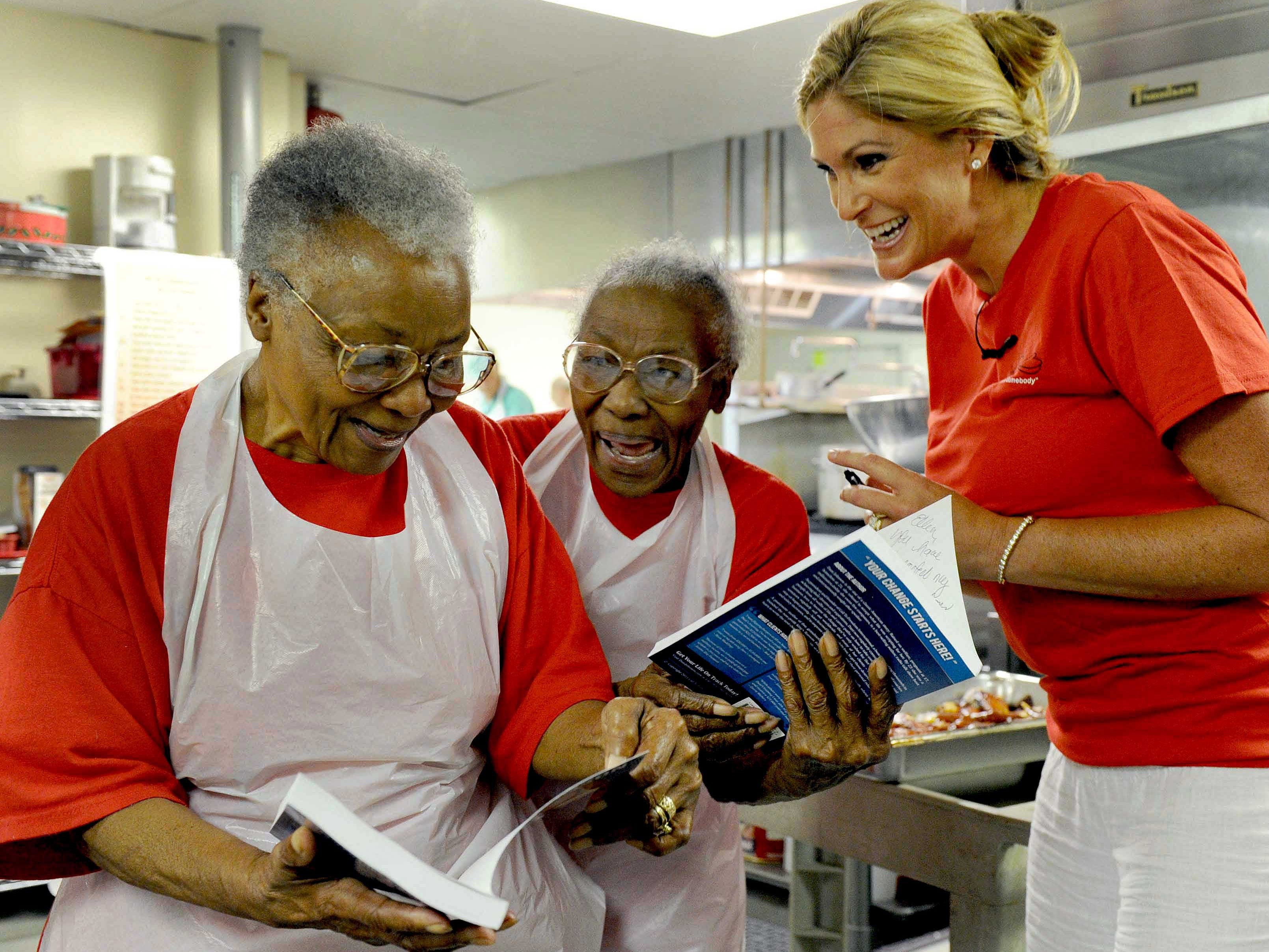 """Dani Johnson, who visited Knoxville as part of ABC's """"Secret Millionaire"""" show, watches as Helen Ashe, left, and Ellen Turner read the inscriptions she wrote for them in her new book. Johnson was back Thursday, Jul. 7, 2011 at the Love Kitchen and worked in the kitchen serving meals for a while."""