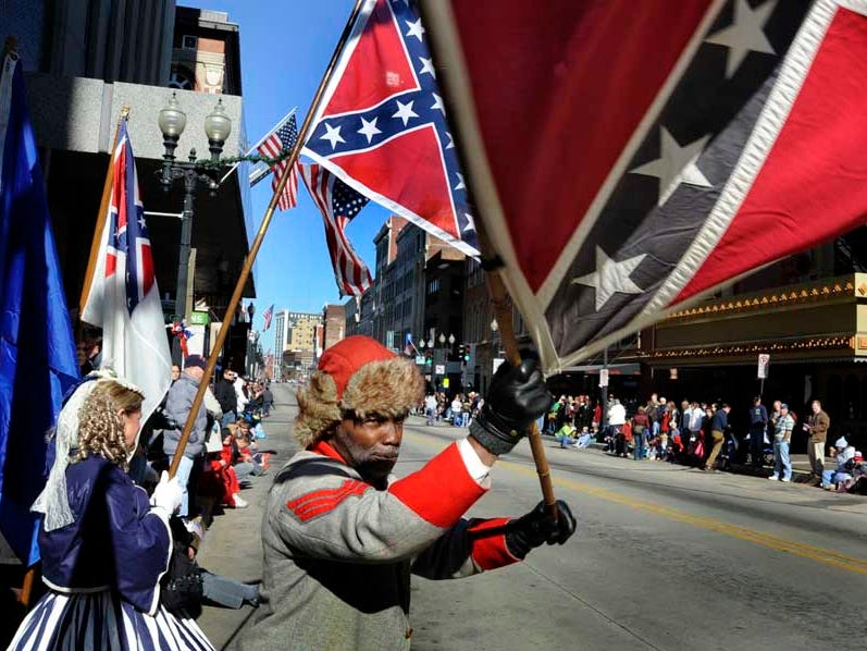 H.K. Edgerton, with the Sons of Confederate Veterans group waves his flag signaling his sighting of the beginning of Knoxville's 86th Veterans Day Parade Friday, Nov. 11, 2011 along Gay Street in Downtown Knoxville.