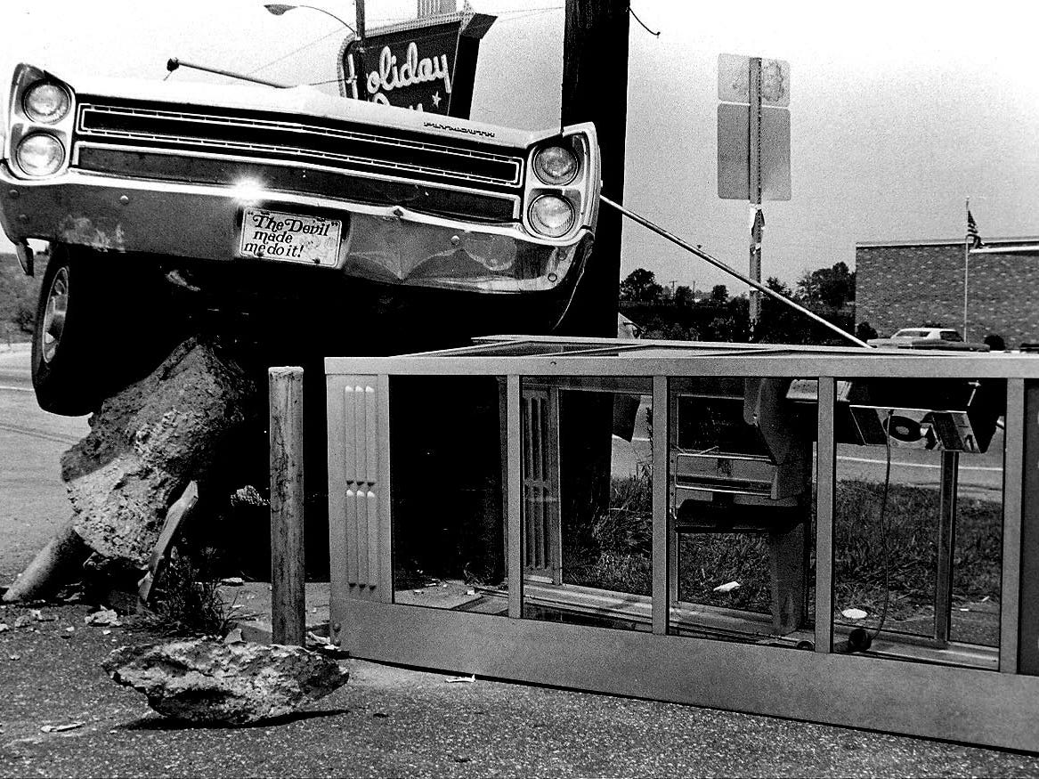 """Vehicle went out of control striking this phone booth occupied by Sharon Dale Taylor, who was injured slightly. Lila Coward Sands was charged with driving with improper equipment. Her front tag says, """"The Devil Made Me Do It!""""."""