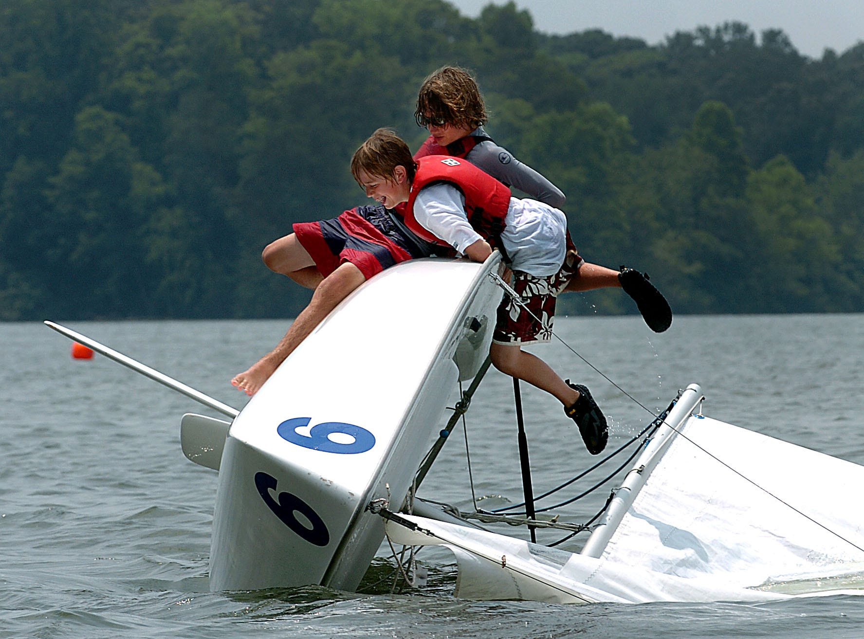 Campers between 9th and 12th grades are learning how to sail or sail better at the 2005 Sail Camp held at the Concord Yacht Club in West Knox County. One of the skills all sailers must learn is how to survive when their boat overturns and how to get sailing again. Ace Englert, front, and Ben Quigley practice during camp Thursday afternoon.
