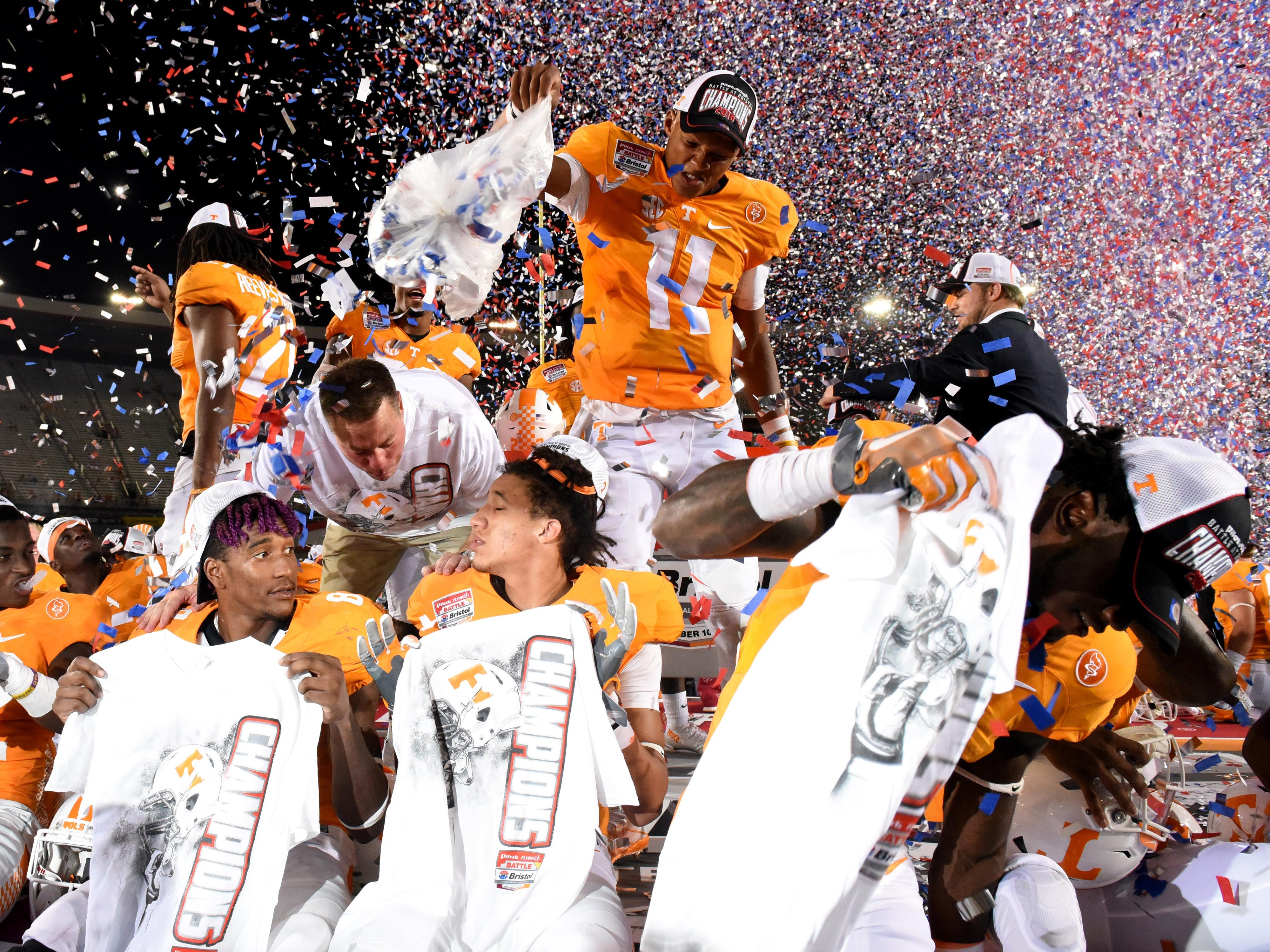 Tennessee quarterback Joshua Dobbs (11) dumps confetti over his Tennessee teammates as they celebrate their 45-24 win over Virginia Tech at The Battle At Bristol Sunday, September 11, 2016 in Bristol, Tenn.
