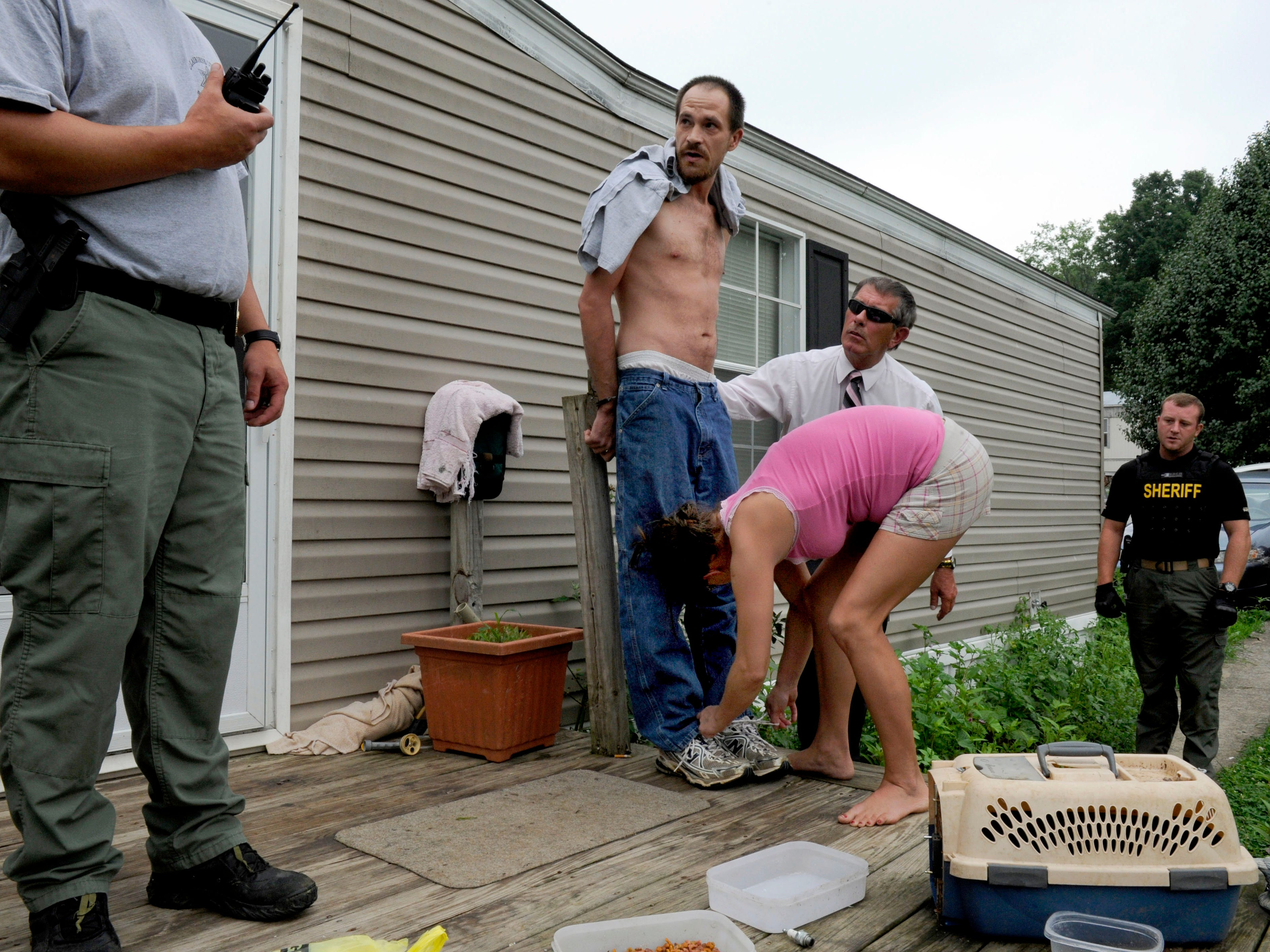 Chris Justice, center in handcuffs, listens to officers as his sister, Fallon Seals, puts on and ties his shoes on the front porch of his grandmother's home where he was arrested Wednesday, Jul. 20, 2011 for sale and delivery of a Schedule II drug following indictments from the Claiborne County grand jury.
