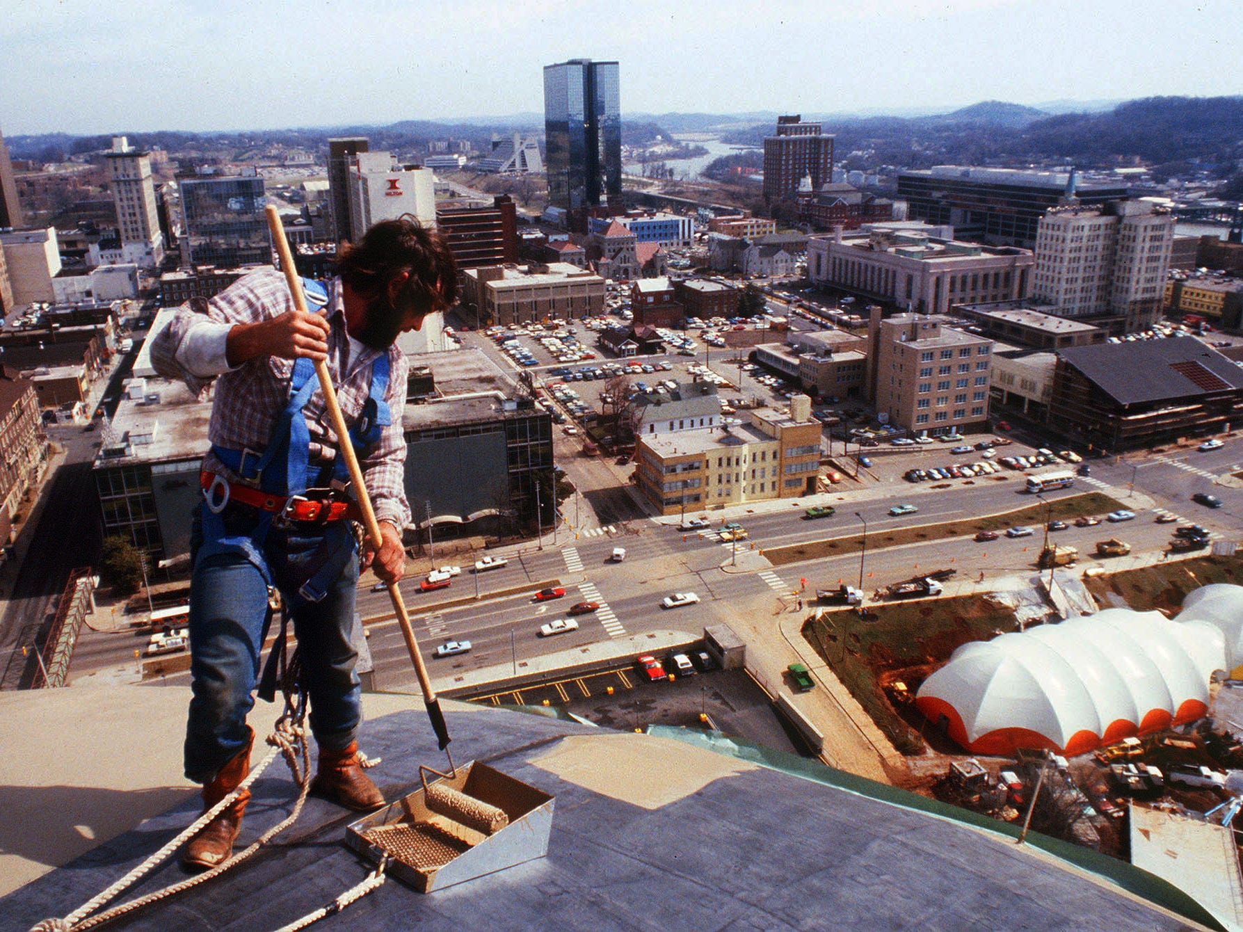 A.C. Cusick with Capitol Roofing Co. keeps his mind on his job and his secure footing as he paints the top of the Sunsphere, 266 feet above the site of the 1982 World's Fair. The rubber roof of the sphere got two coats of gold paint to match the gold glass in the sphere.