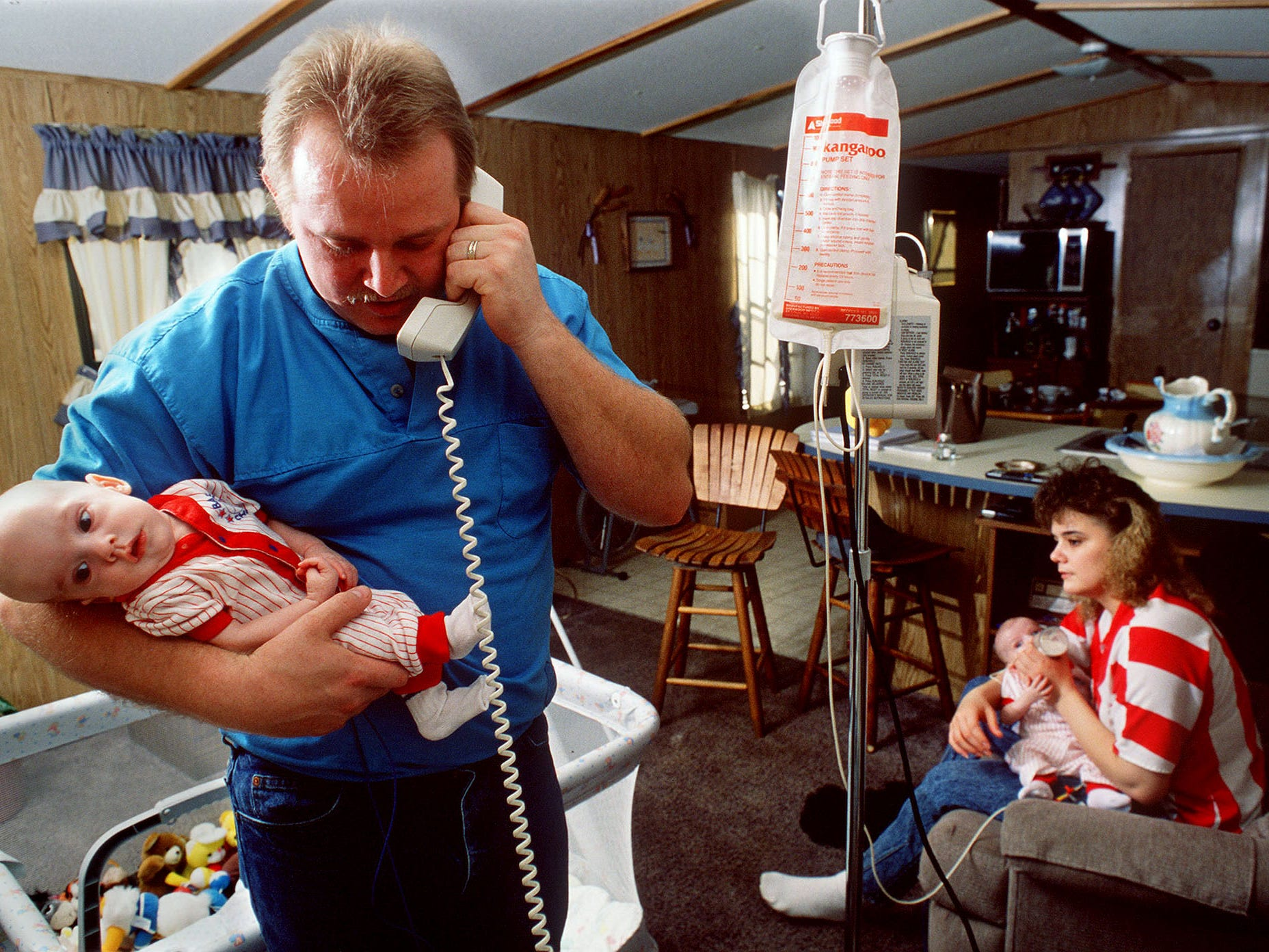James Epps, holding his son, Bryan, answers the phone as Tracie Epps feeds the twin brother, Joshua. Their twins are still recovering after surgery to separate the conjoined twins. Feb. 5, 1990