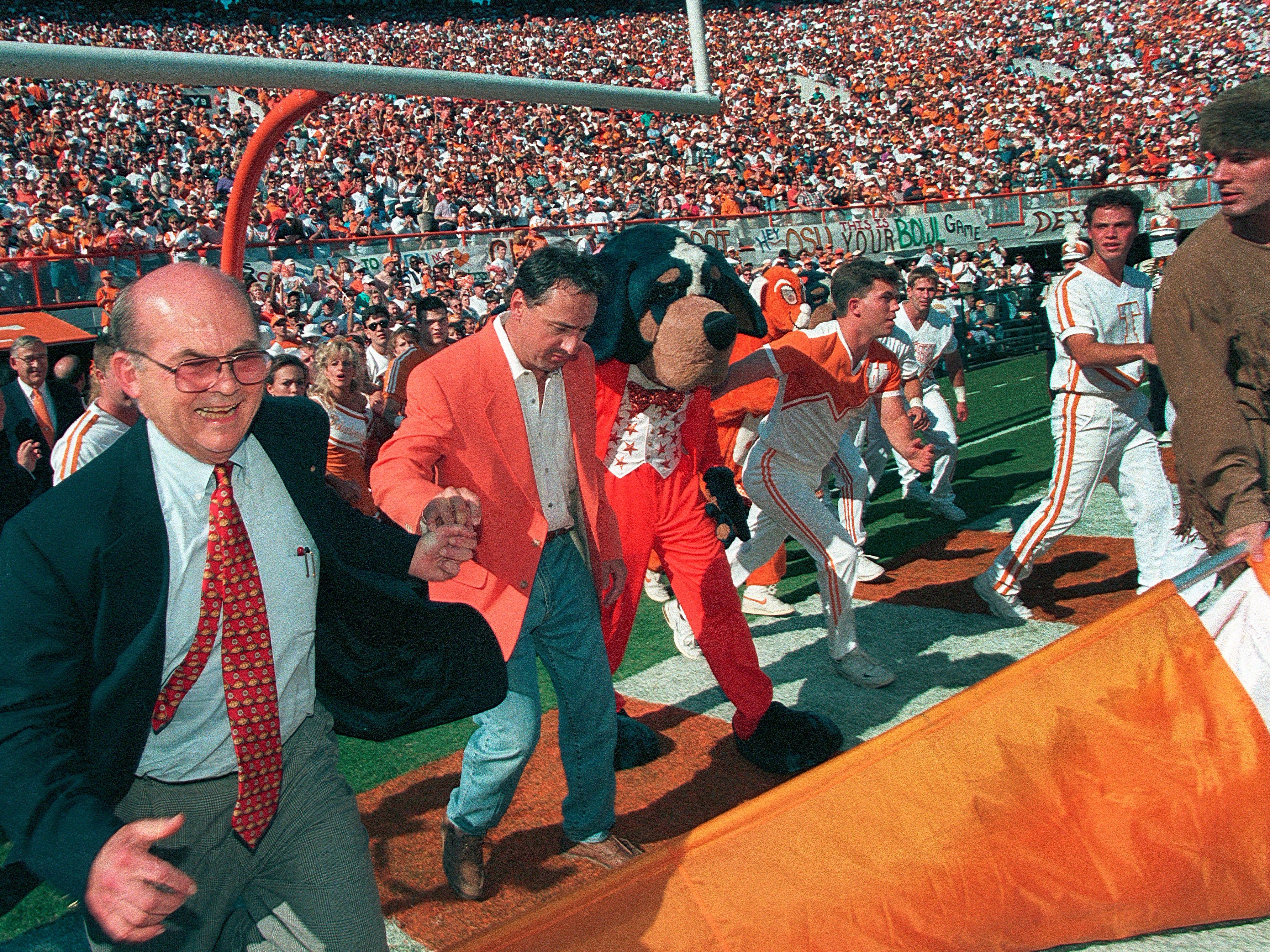 "University of Tennessee President Joe Johnson, left, and Chattanooga businessman John 'Thunder' Thornton run through the ""T"" before the Oklahoma State game Sept. 30, 1995. Thornton donated $1 million to the university and asked if he could run through the ""T"" in return."