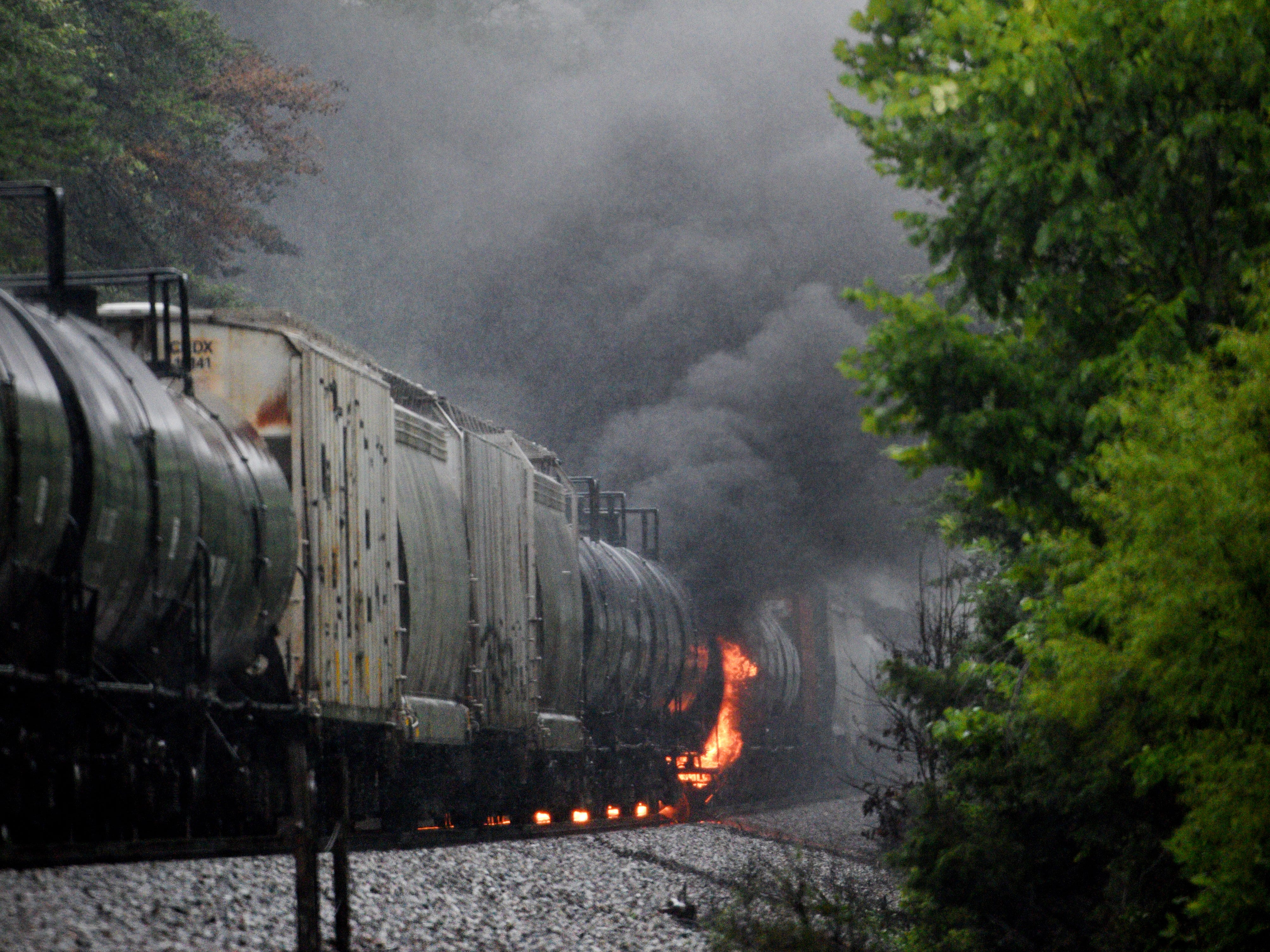 """Smoke rises from a CSX train following the derailment of a tank car carrying a """"highly flammable and toxic"""" gas Thursday, July 2, 2015, in Maryville, Tenn. The single tank car loaded with acrylonitrile, a hazardous material used in a variety of industrial processes including the manufacture of plastics, forced an evacuation of residences and businesses in a two-mile radius."""