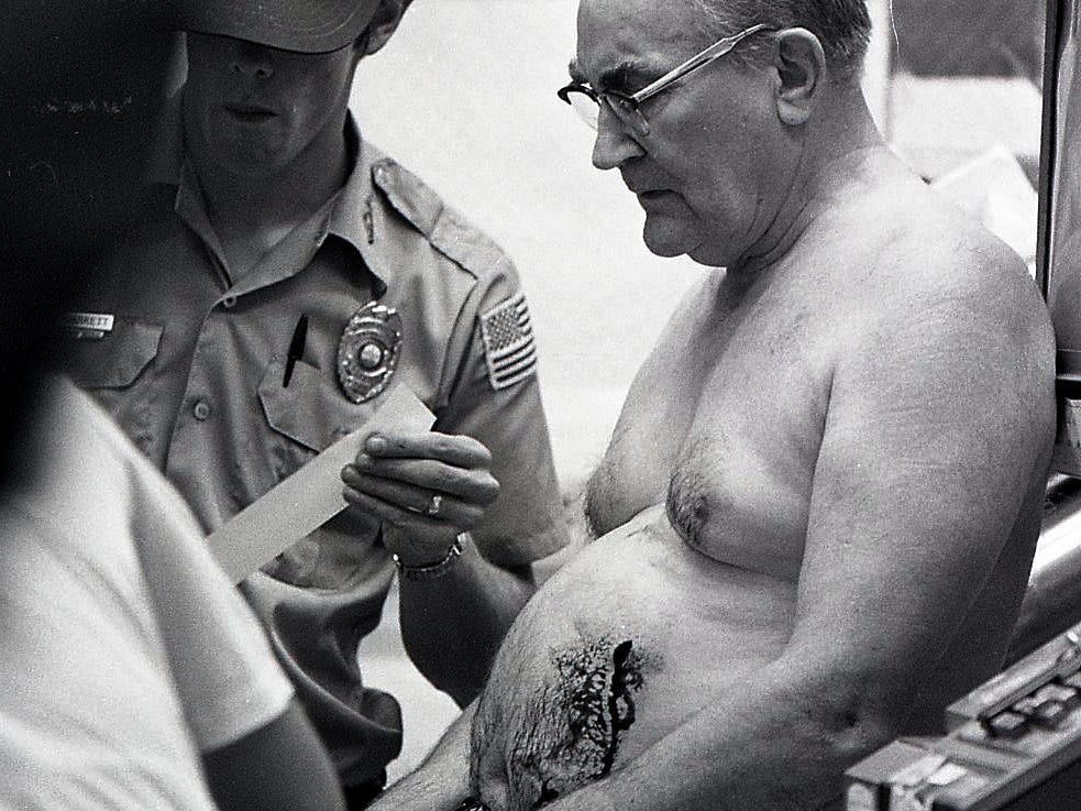 Knox County Ambulance Service attendants treat 69-yer-old Herb Ward after he was stabbed by a robber as he opened Weigel's Jug-O'Mild Store on Magnolia Ave, early July 9, 1979. The wound is visible on Ward's stomach along with an empty cash register.